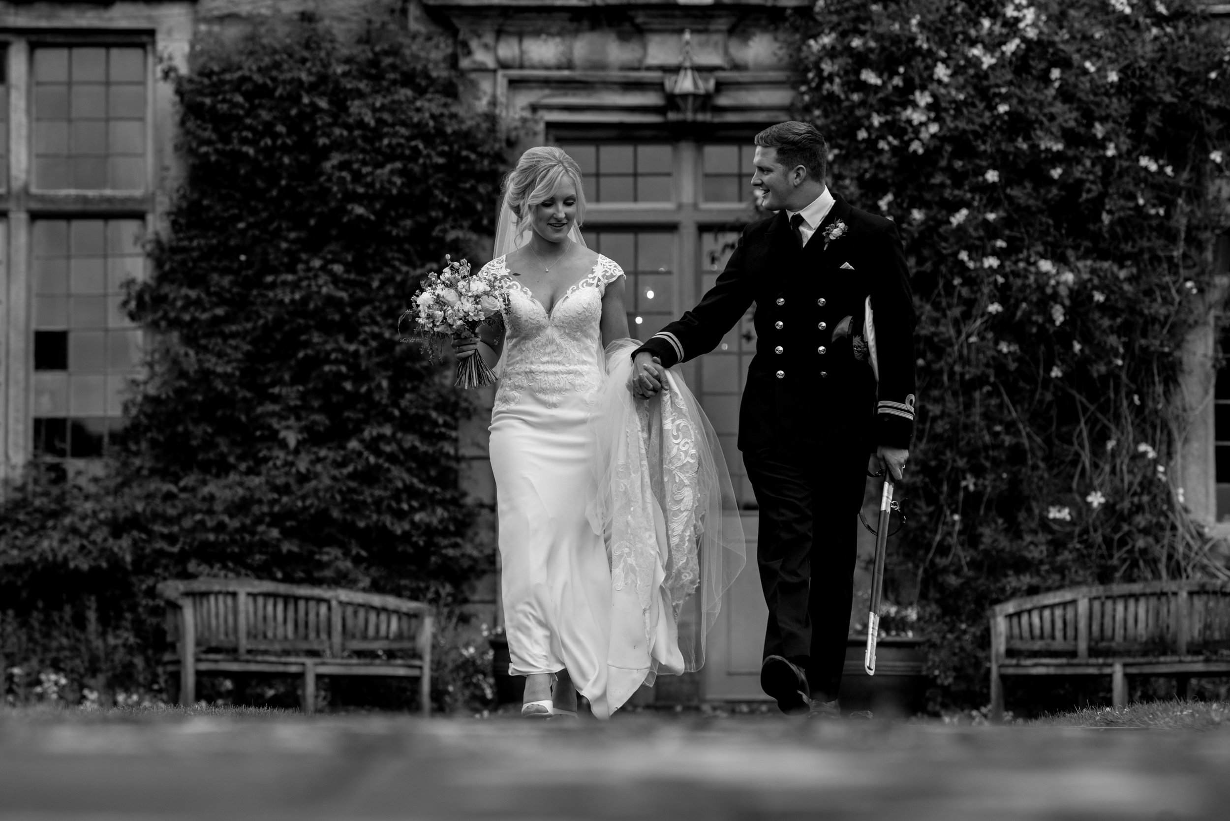 The bride and groom walk away from Askham Hall during their wedding photography session