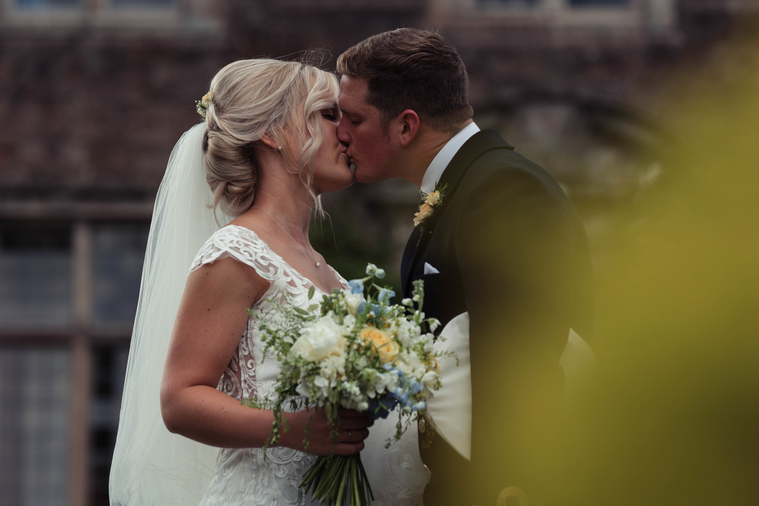 The light on the bushes reflects on the bride and grooms face as they share a kiss