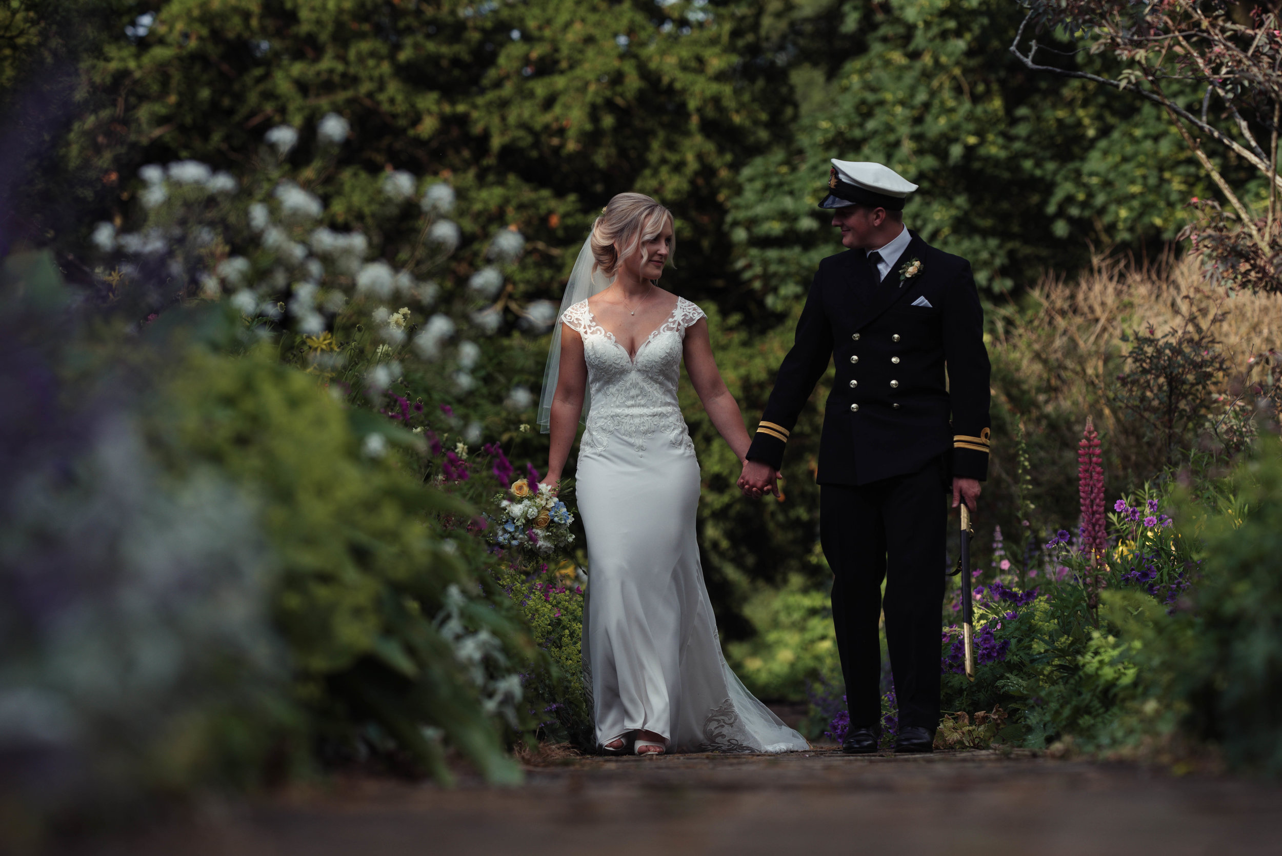 The bride and groom walk among the flowers at Askham Hall