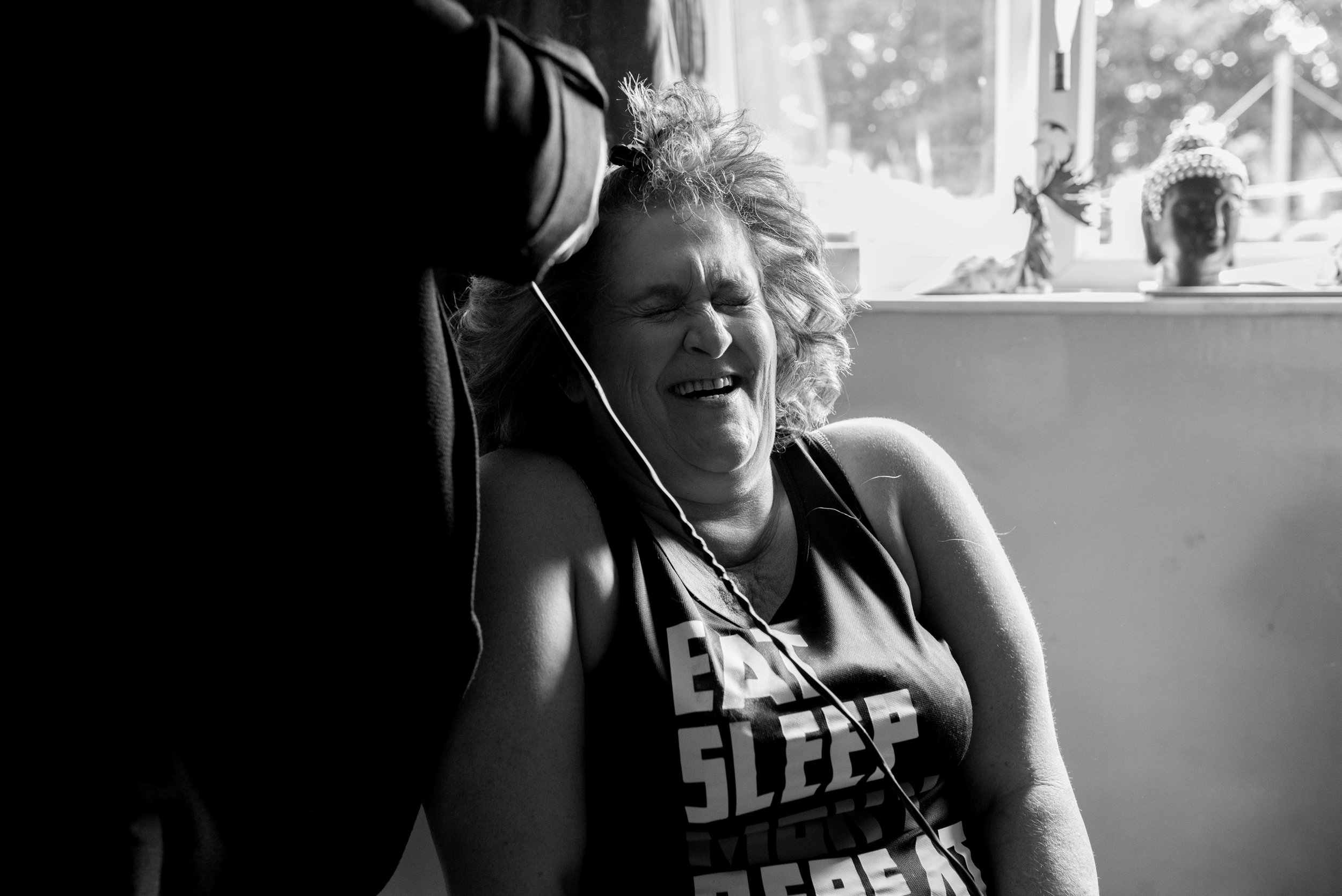 Curly haired bride laughs her head off while she's getting her hair ready for the wedding
