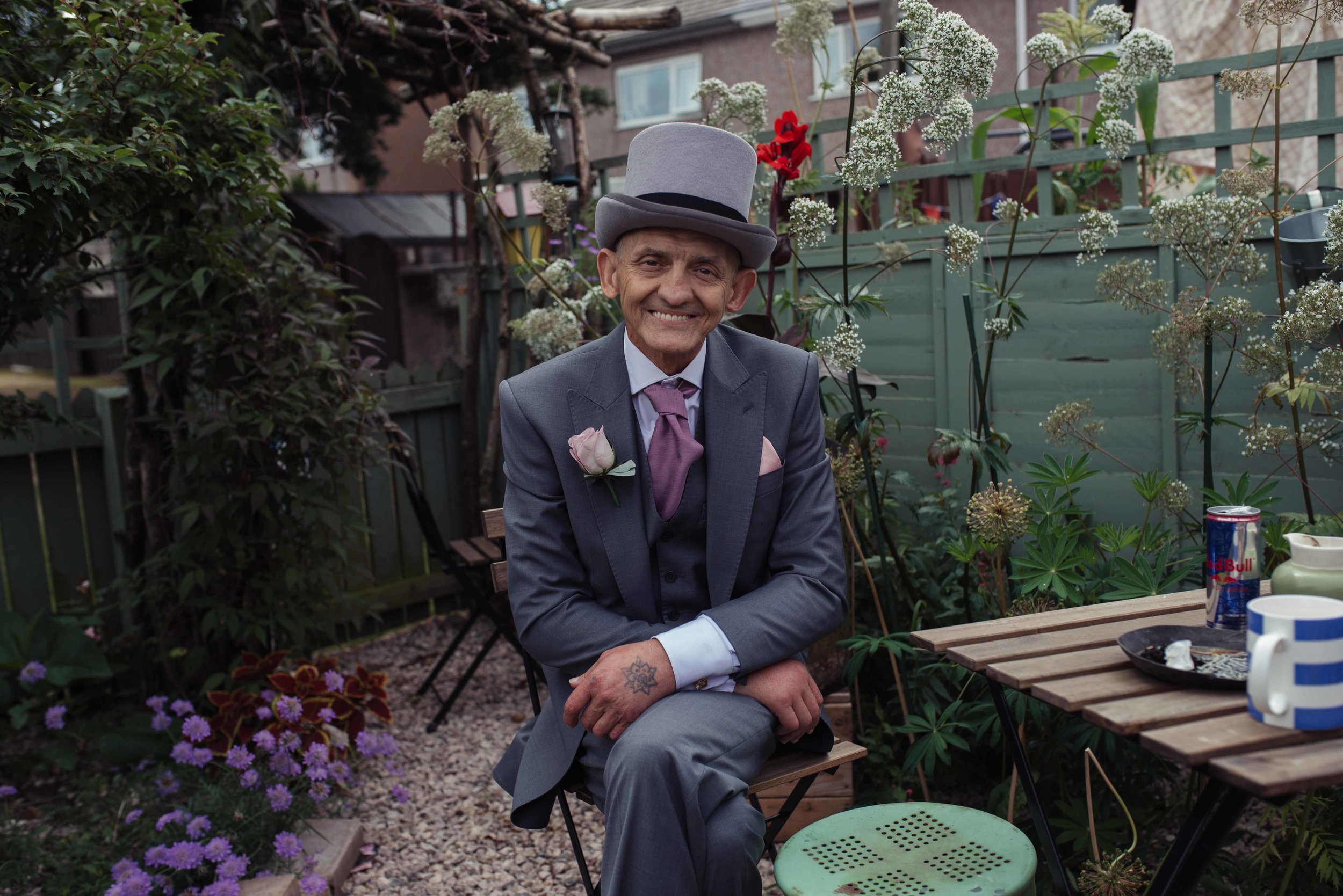 Groom sits posing for a photo in his neighbours garden