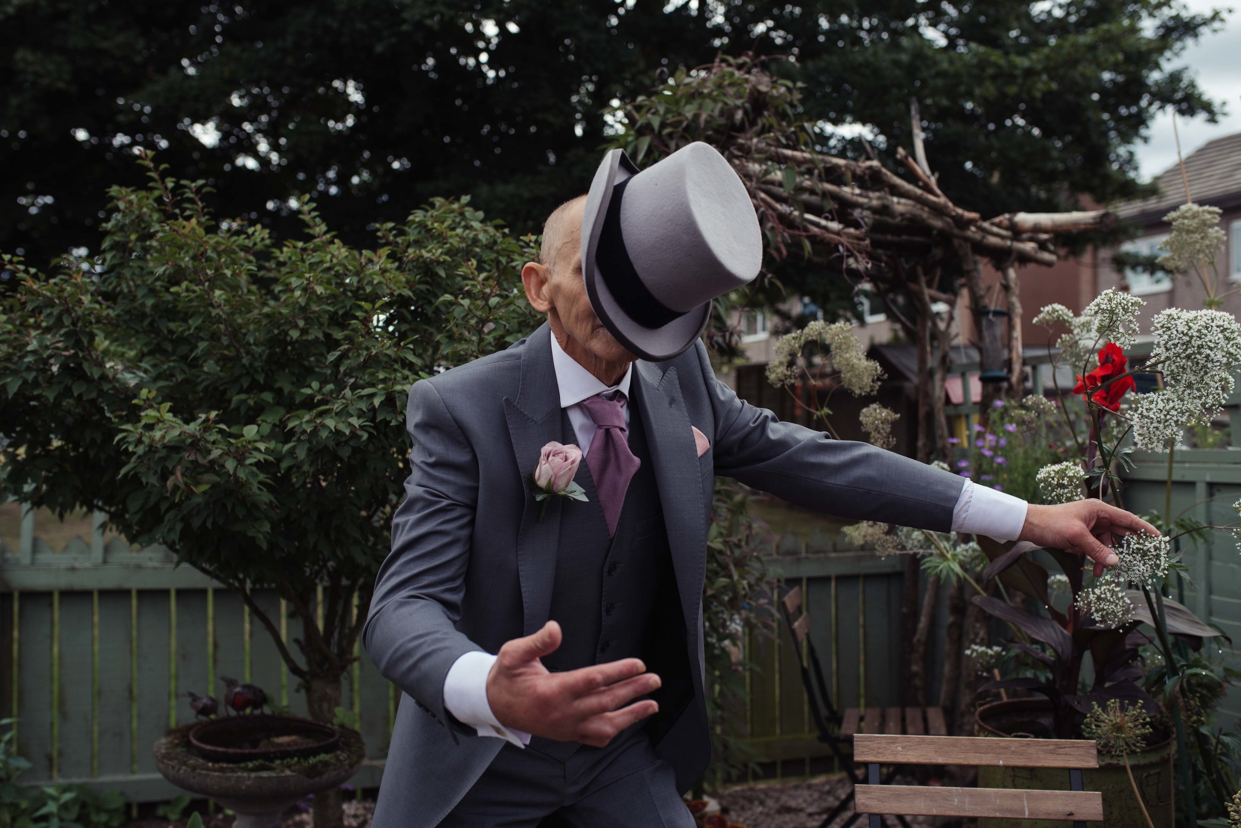 Groom in his neighbours garden tries to flip his hat onto his head