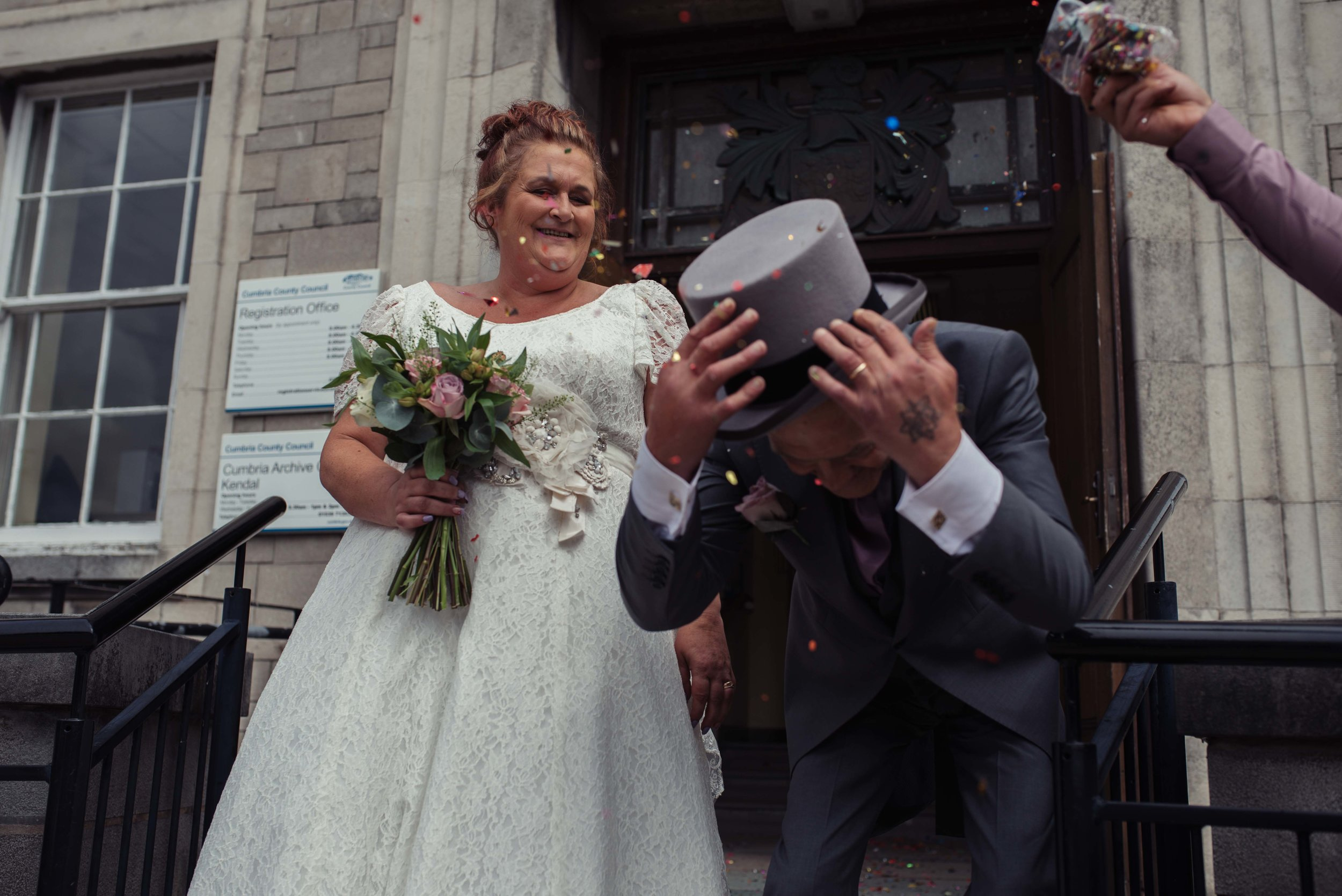 Confetti almost knocks the grooms hat off outside the cumbria wedding venue