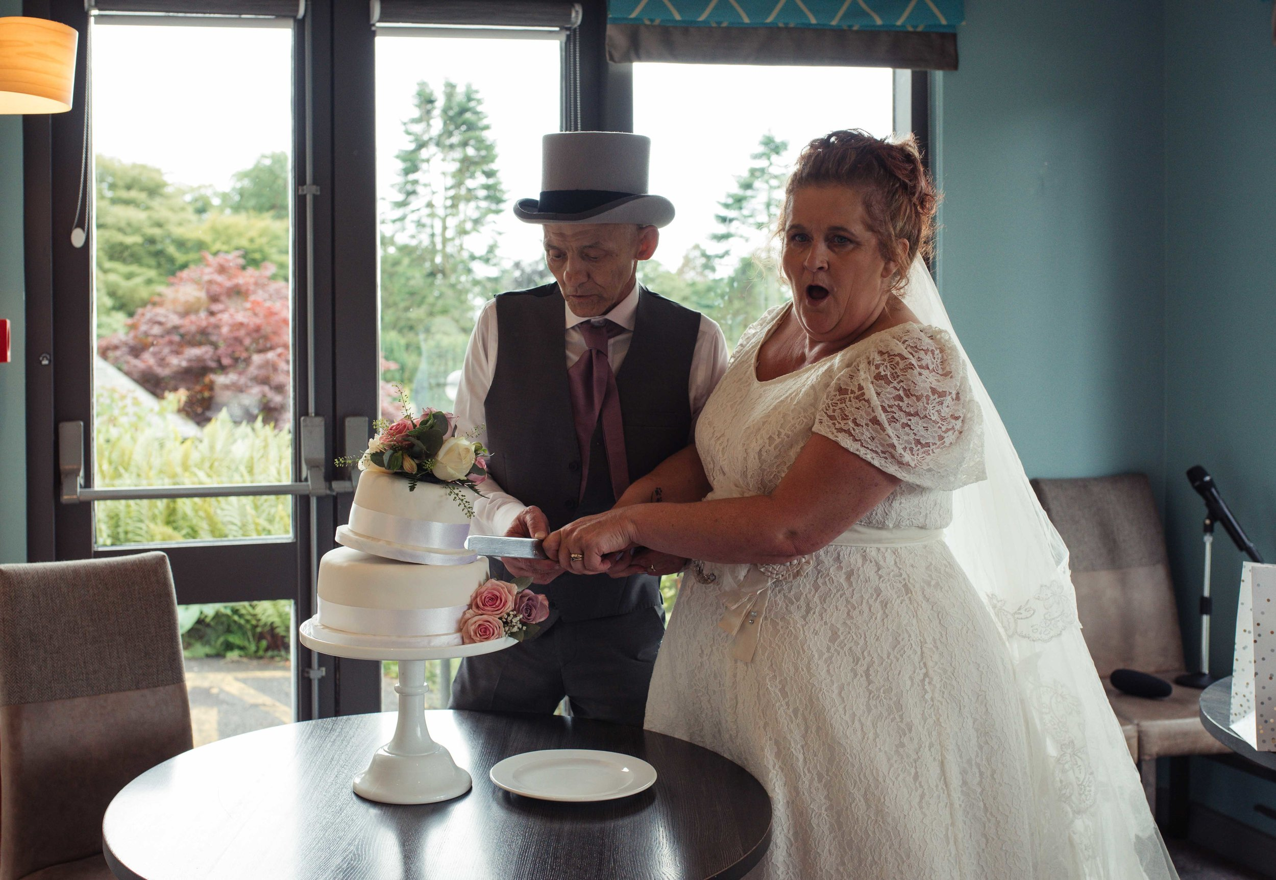 The bride and groom almost make the cake topple as they cut it in the greenhouse restaurant