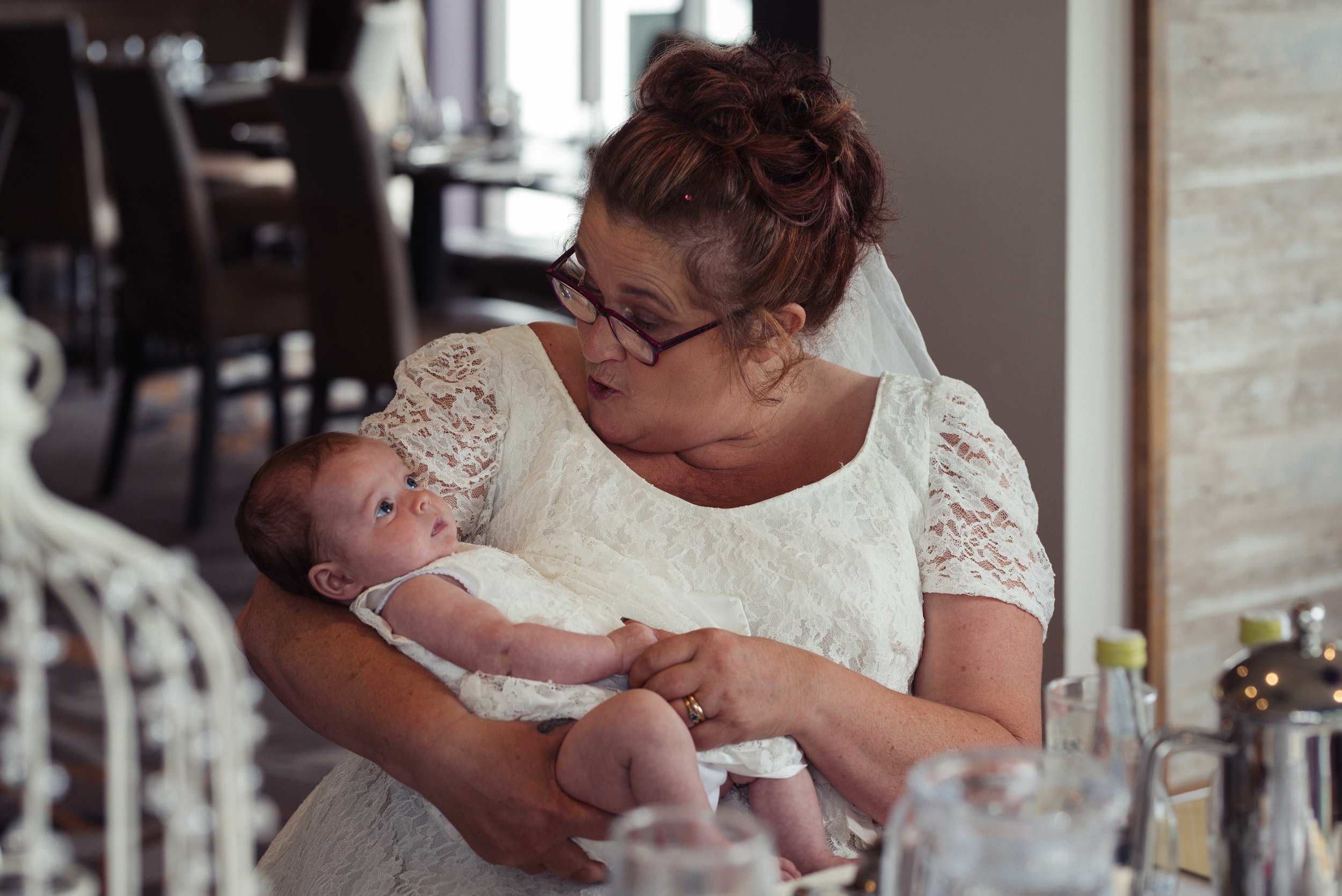 The bride holds a newborn baby wedding guest
