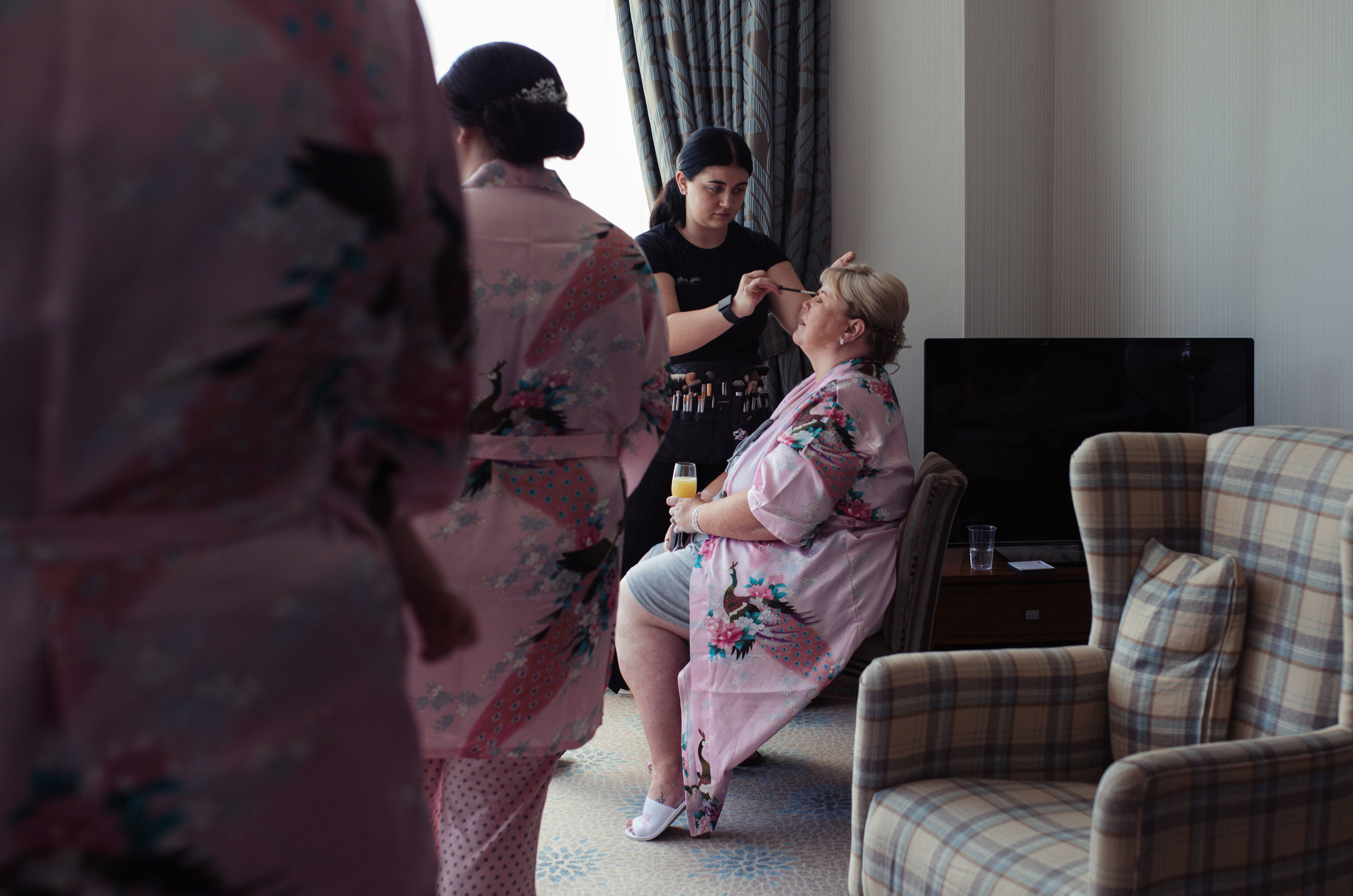 Mother of the bride sits to have her make up done