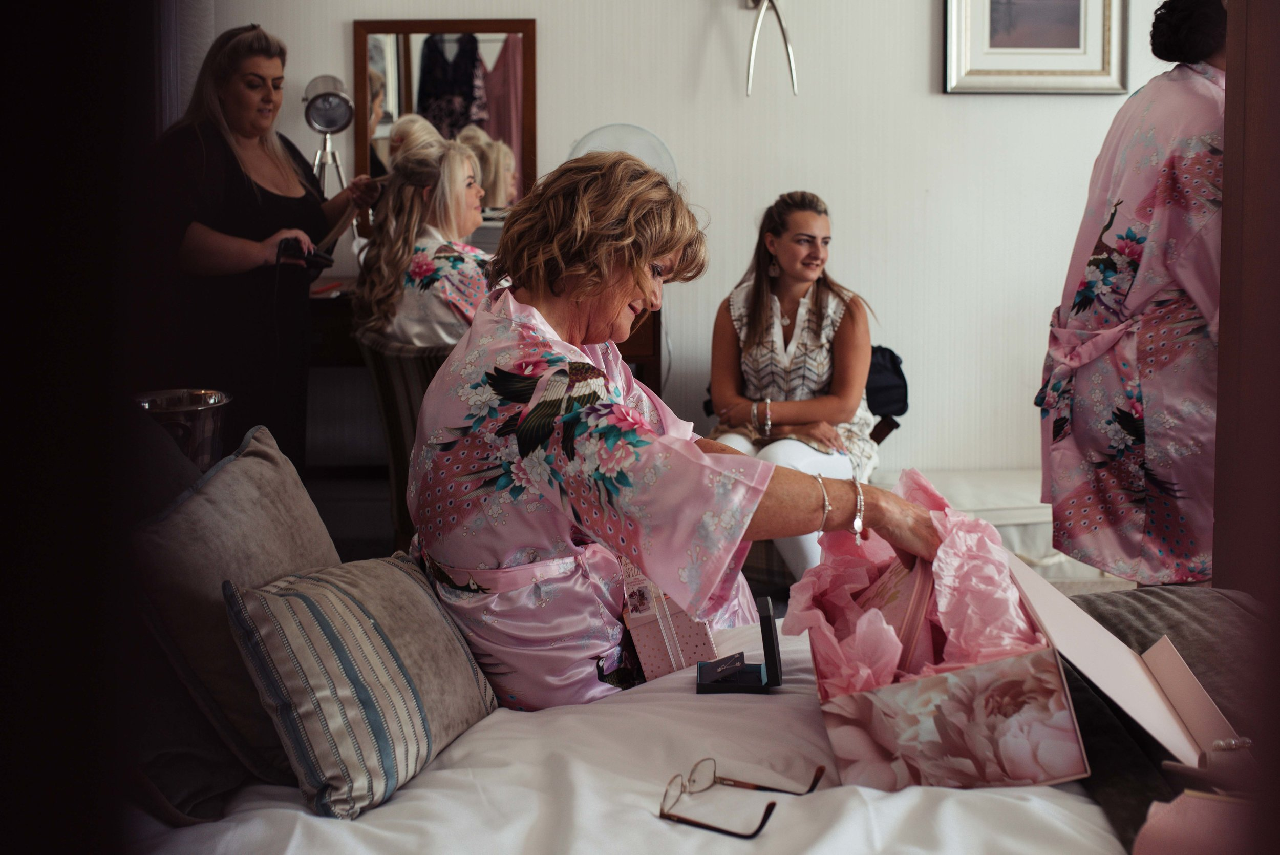 The auntie of the bride sits on the bed and looks at her wedding gifts