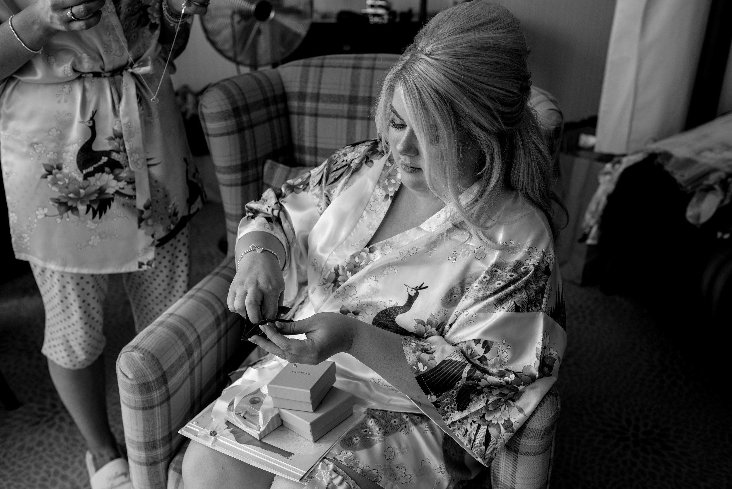 The bride sits and opens her presents off her new groom