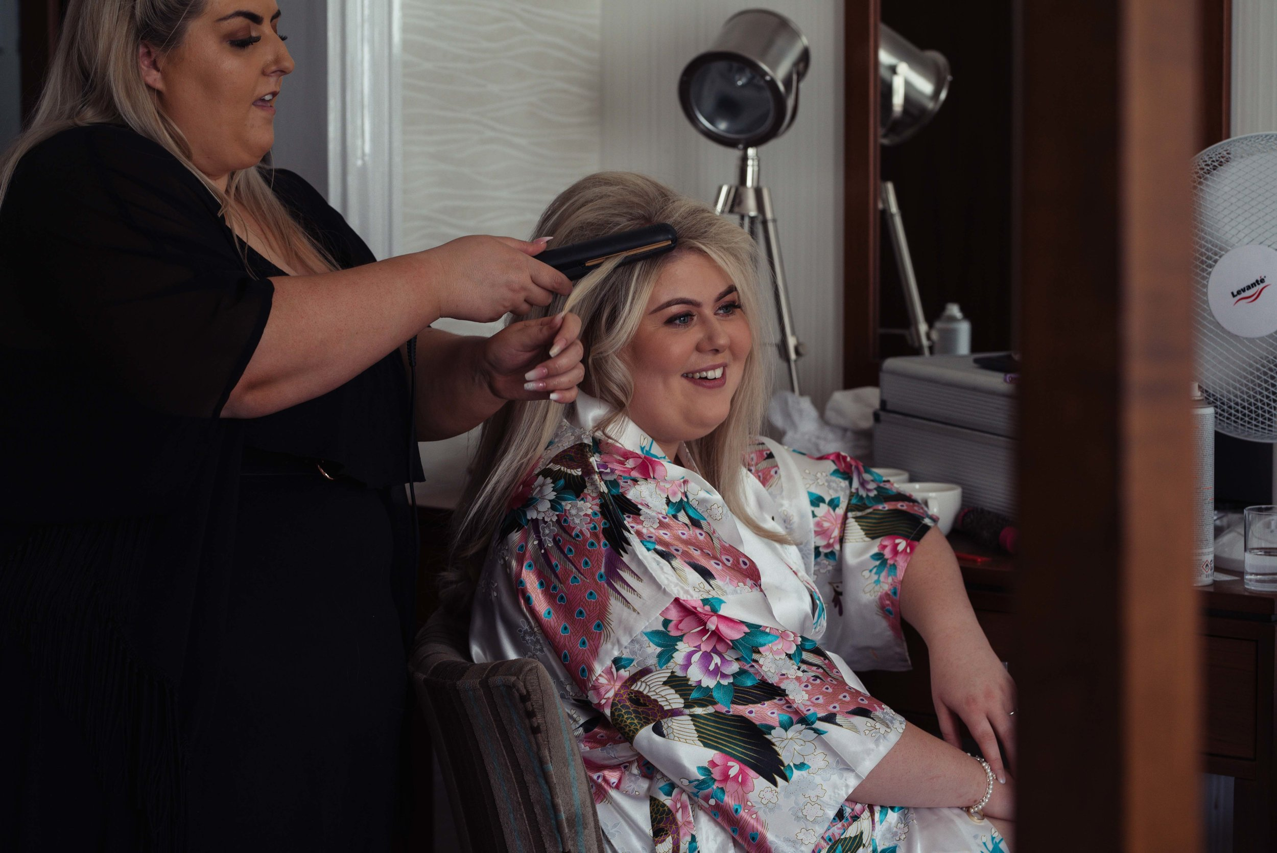 The bride has a giggle as she gets her hair done