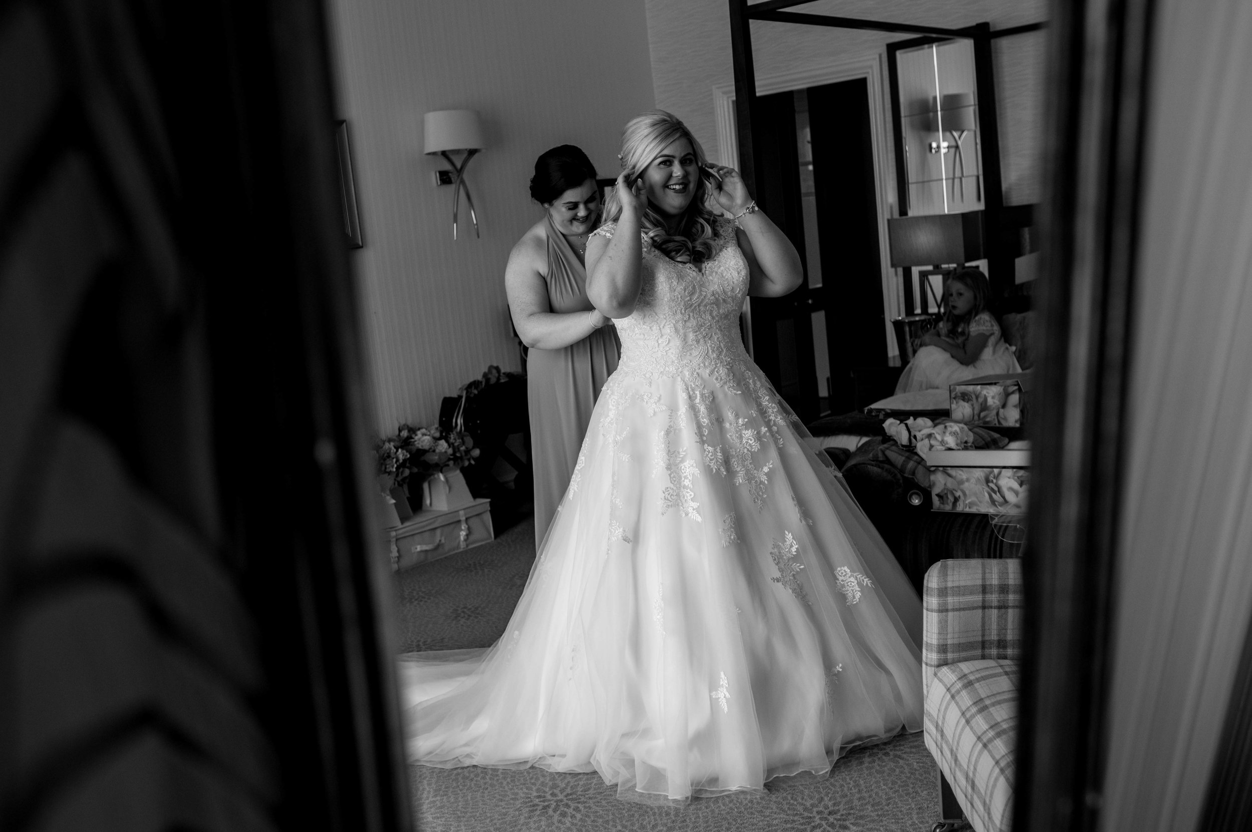 The bride laughs as she's getting her wedding dress on