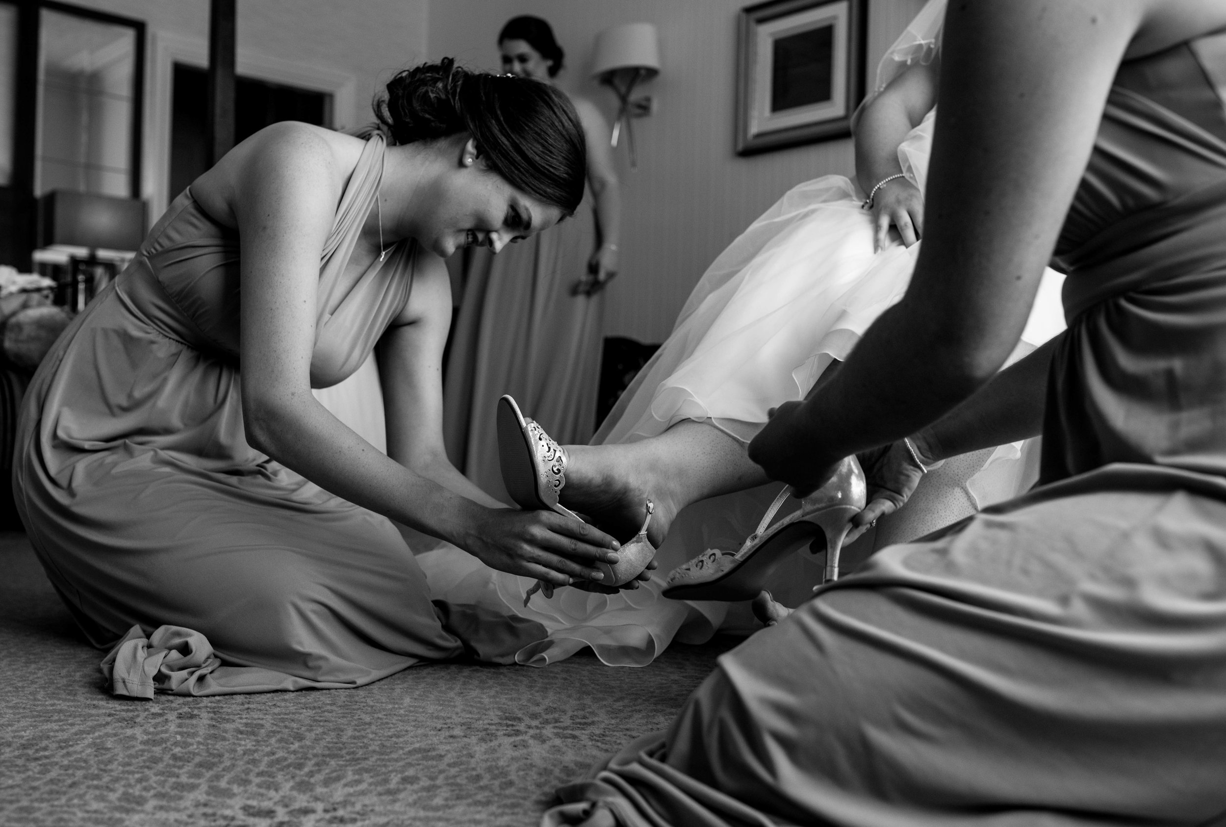 Bridesmaids gather together to help put the brides wedding shoes on
