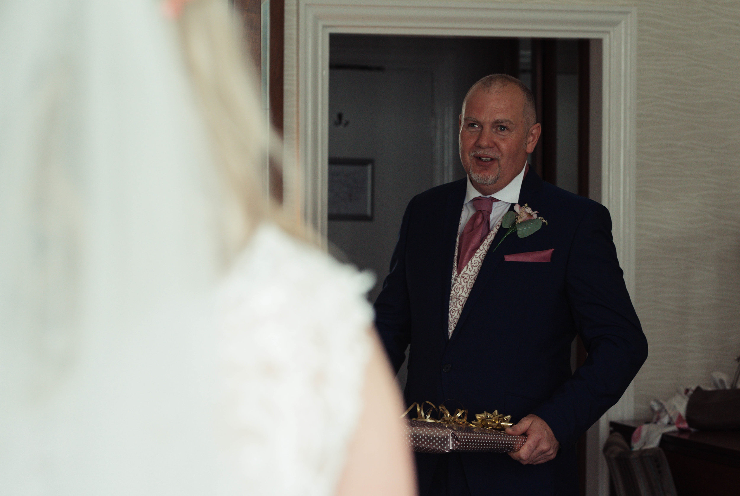 Father of the bride sees his daughter for the first time in a wedding dress