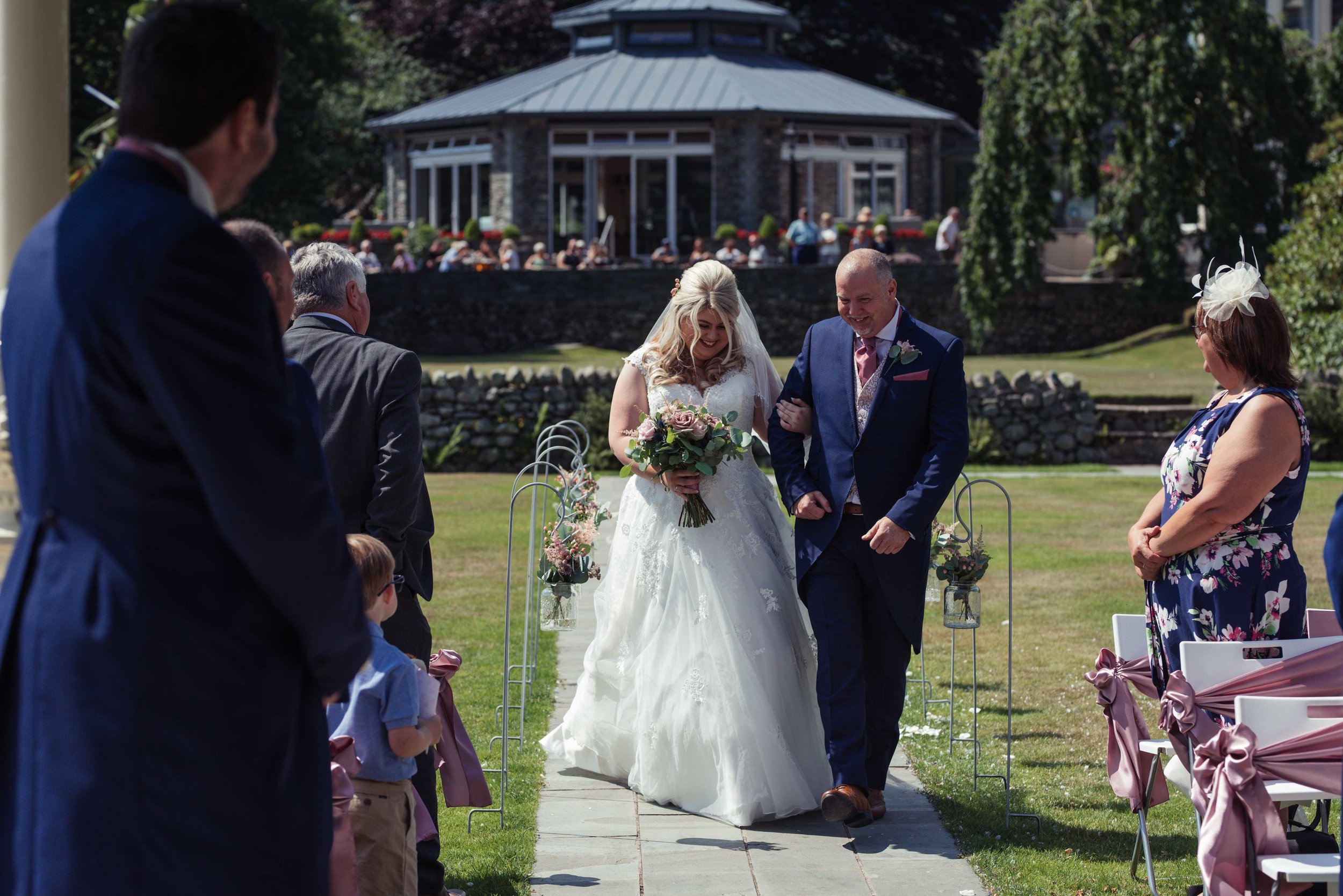 The brides father escorts his daughter down the aisle at the Inn on the Lake