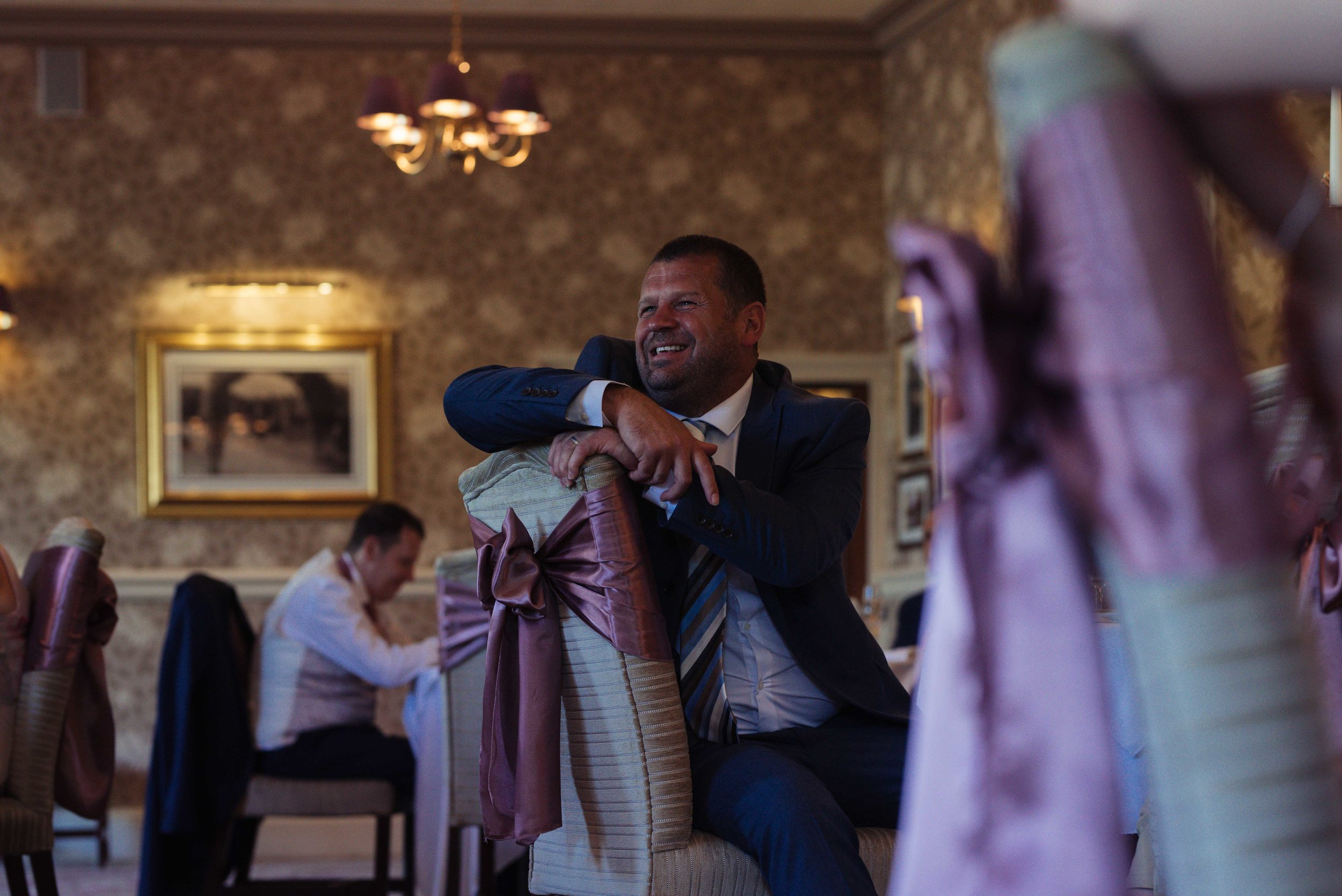 wedding guest leans over the edge of a chair to watch the speeches