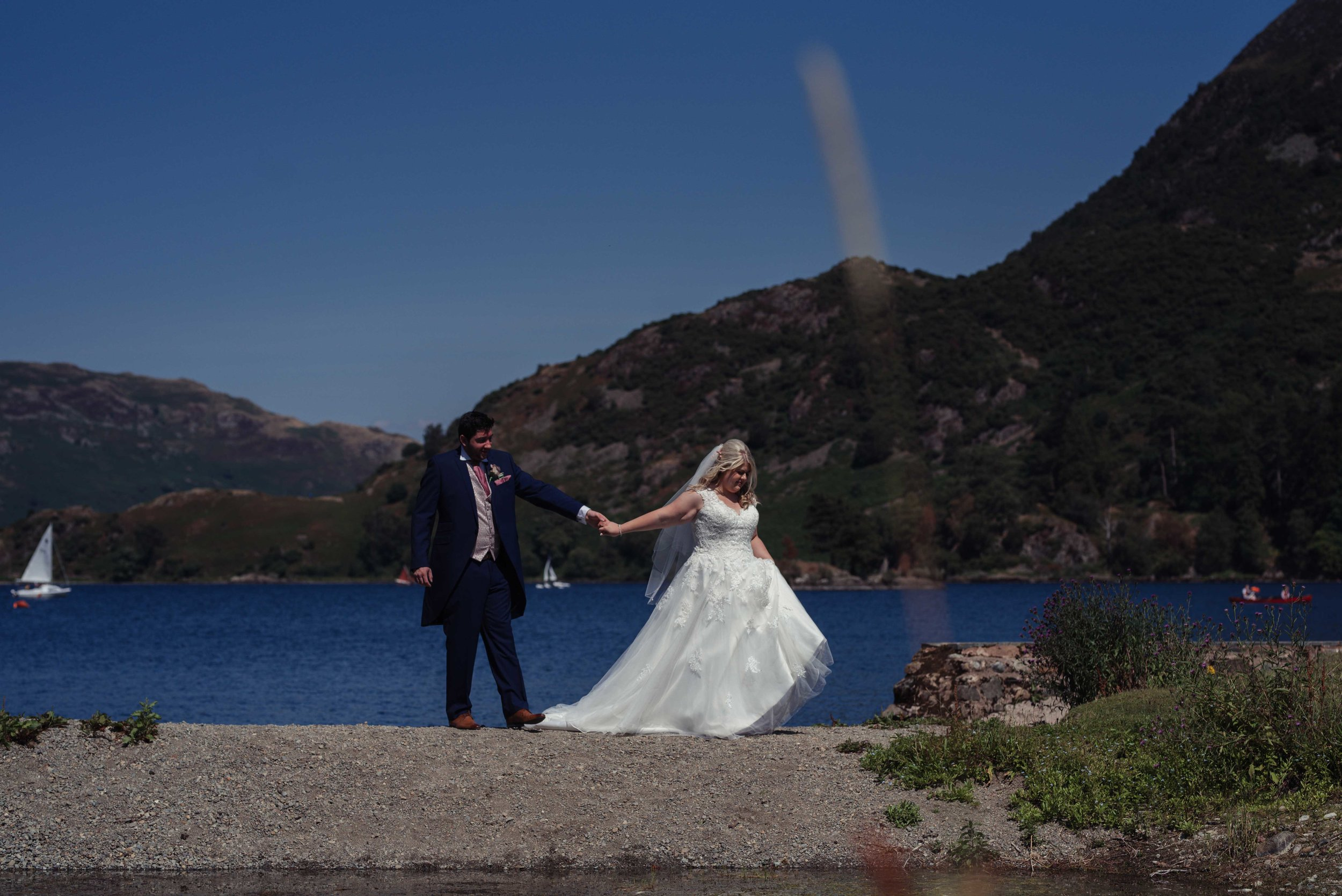 The bride and groom have a walk at the edge of the lake at the inn on the lake