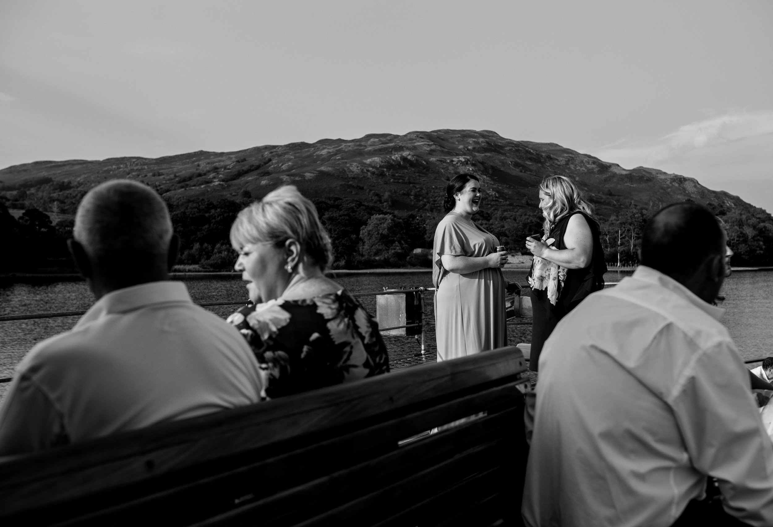 A couple of wedding guests stand on the boat and chat to each other