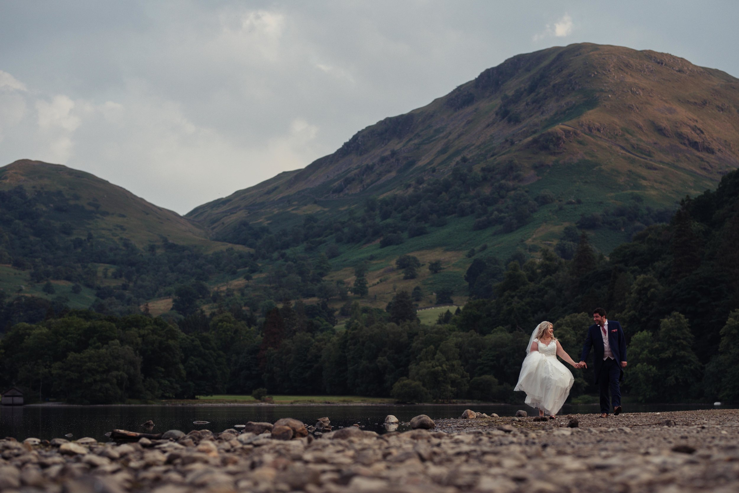 The bride and groom walking on the shores of Ullswater
