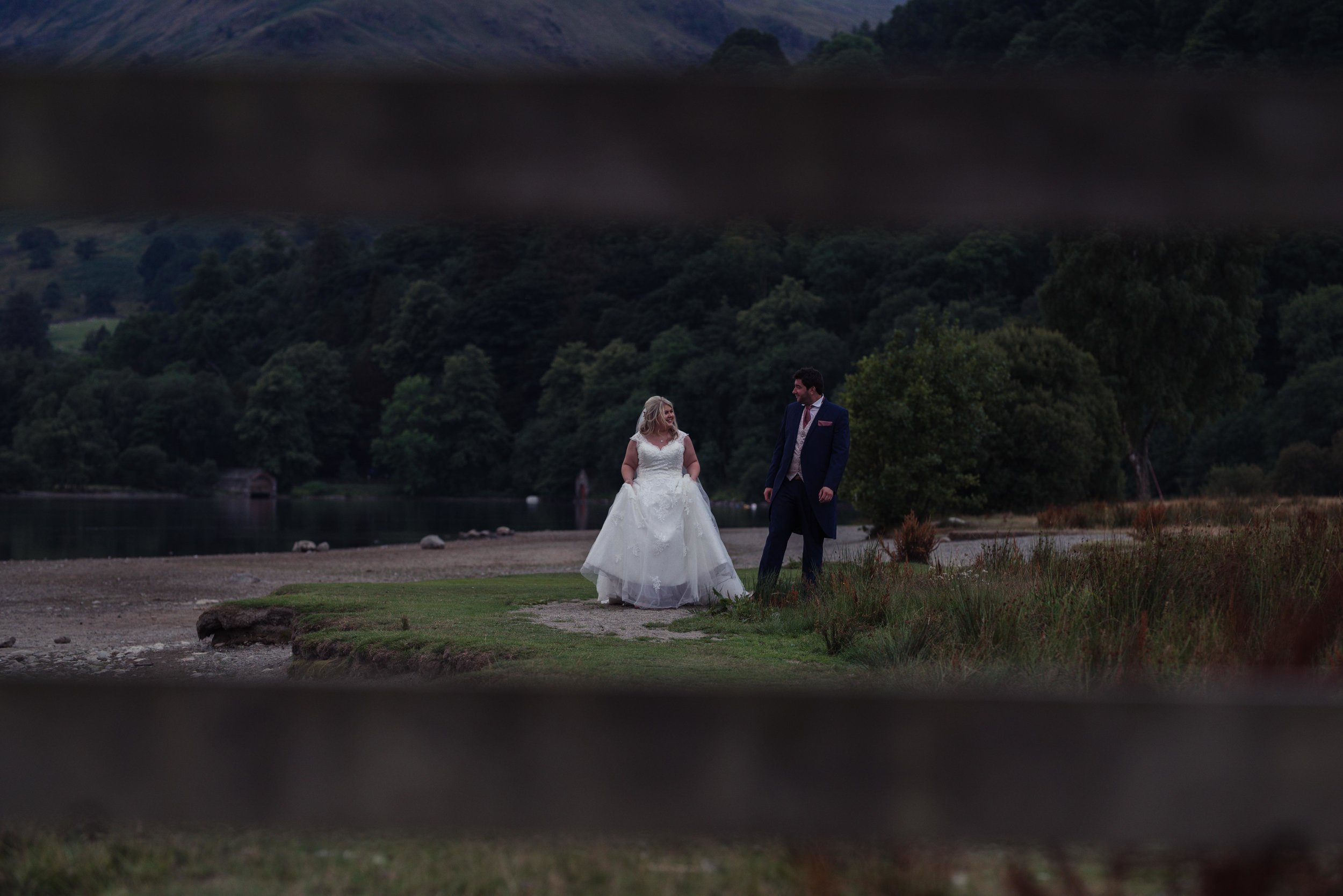 The bride and groom walk alongside the lake