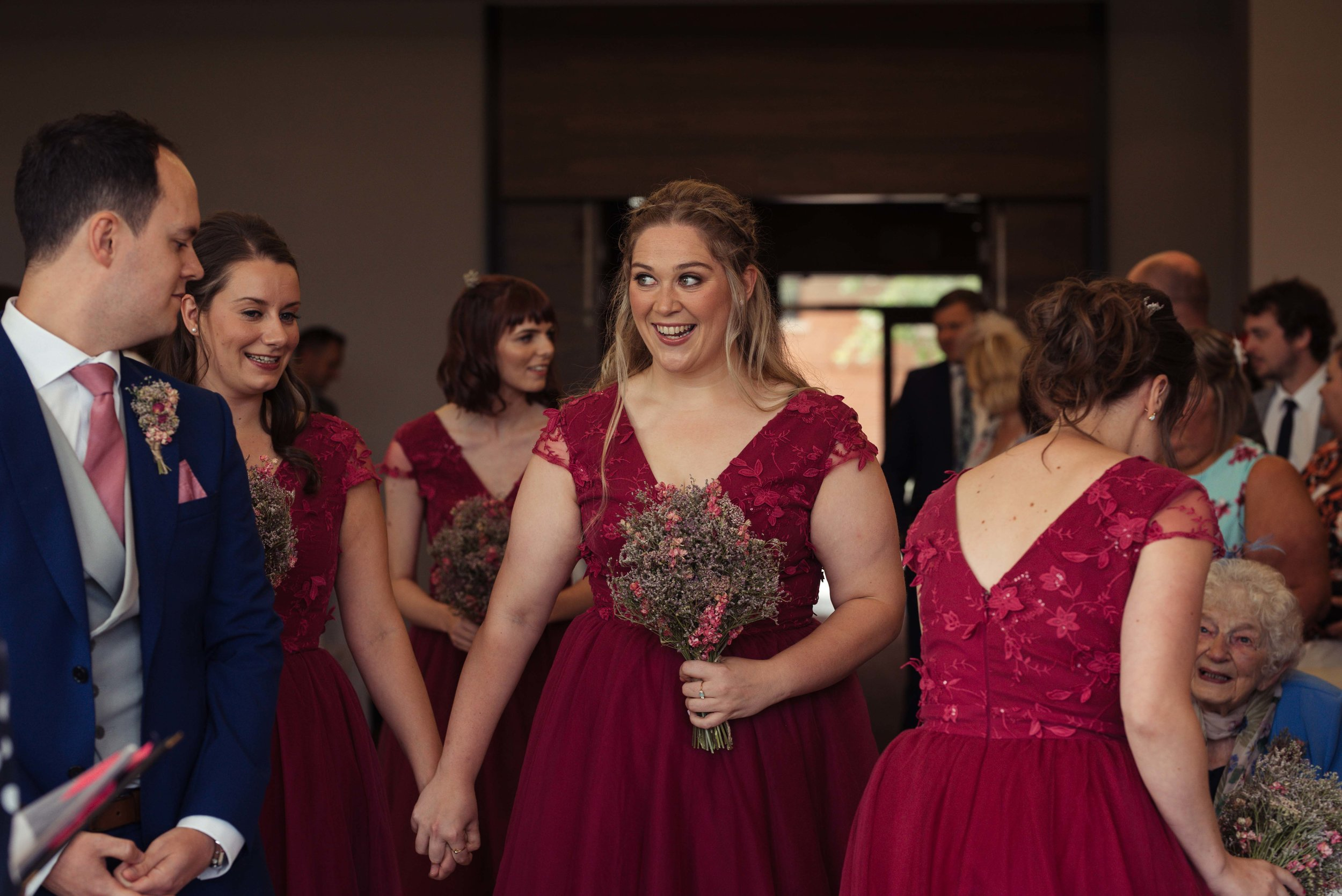 A happy bridesmaid walking up the aisle at the start of the wedding ceremony