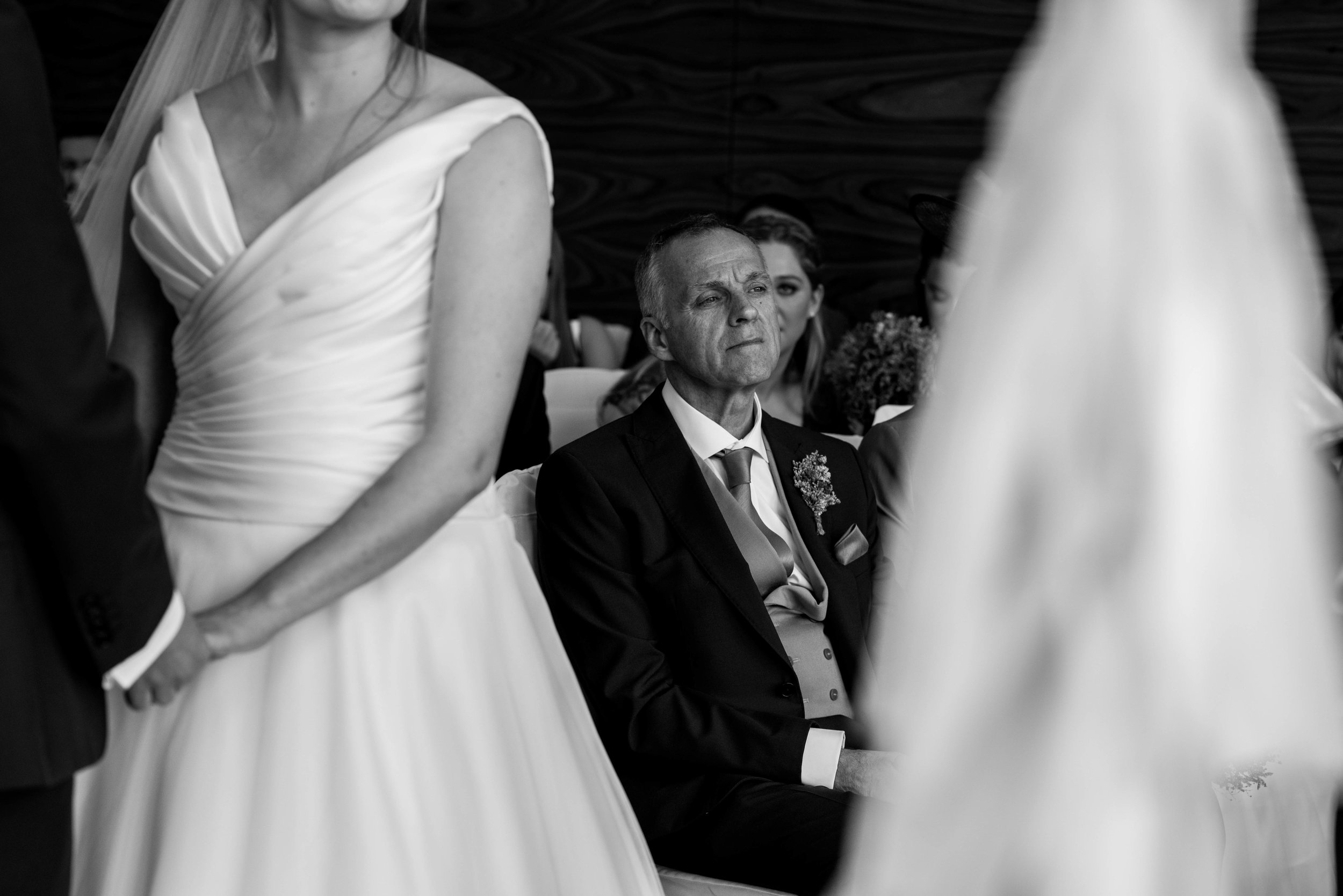 The brides father sits looking emotional during the wedding ceremony
