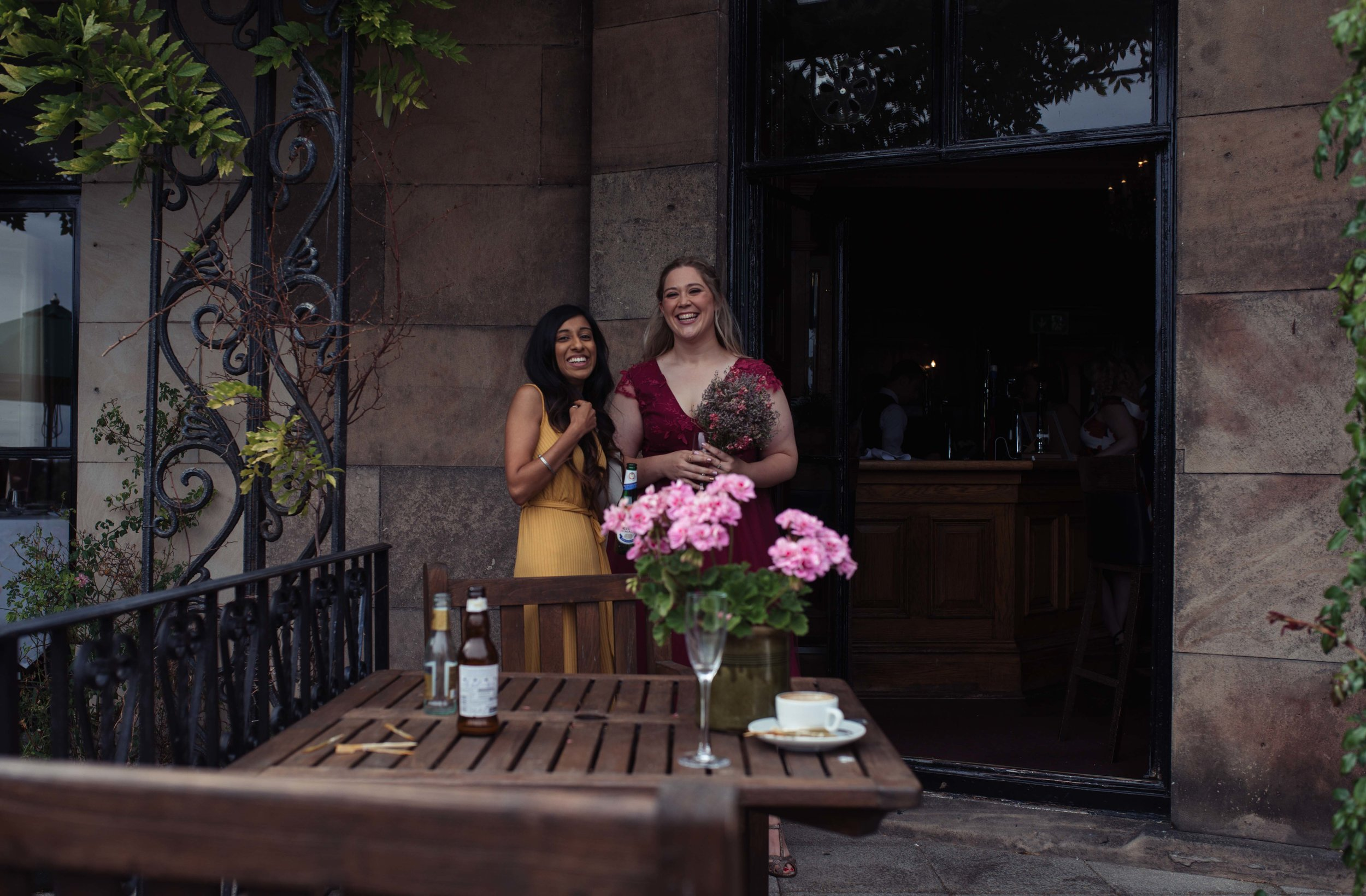 Two wedding guests stand chatting outside rookery hall