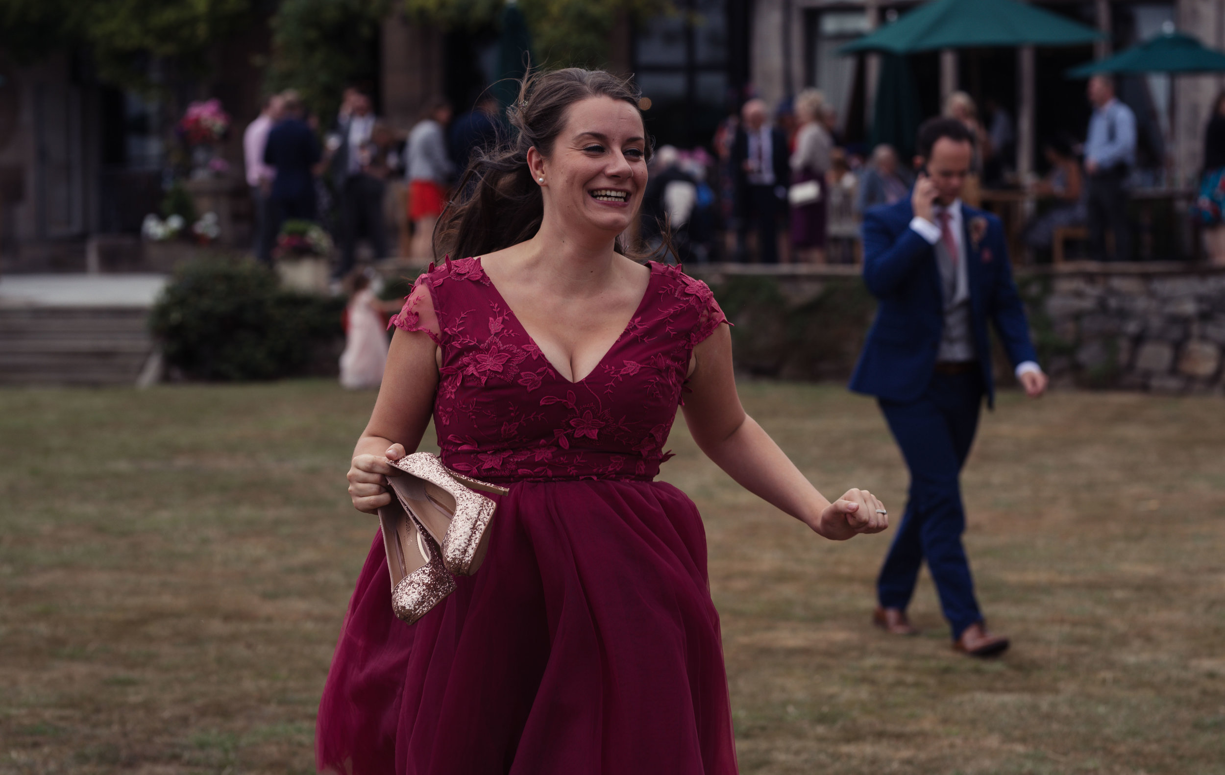The bridesmaid runs towards the other bridesmaids with her shoes off