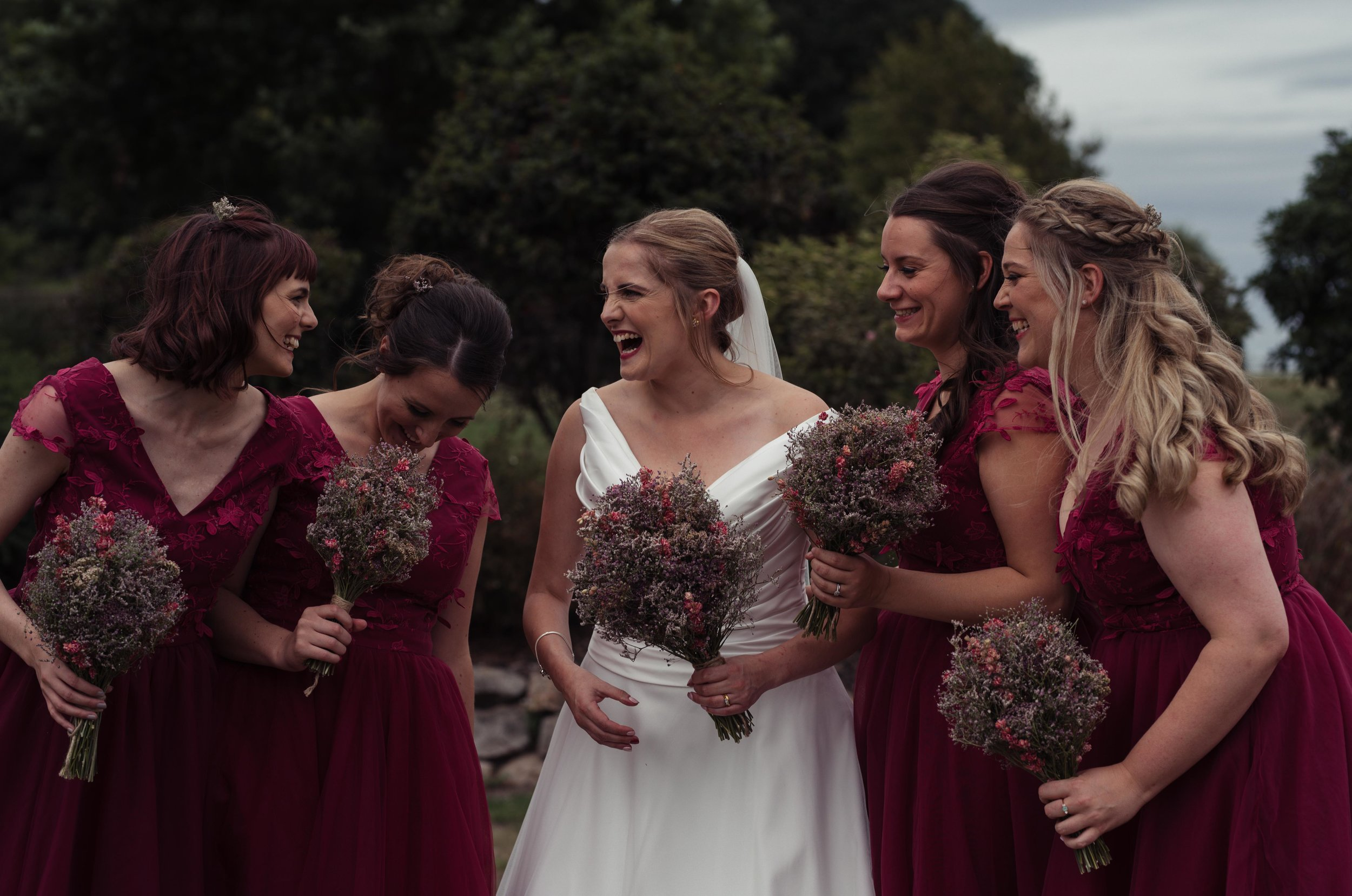 The bride and her bridesmaids having a laugh together during the photo shoot