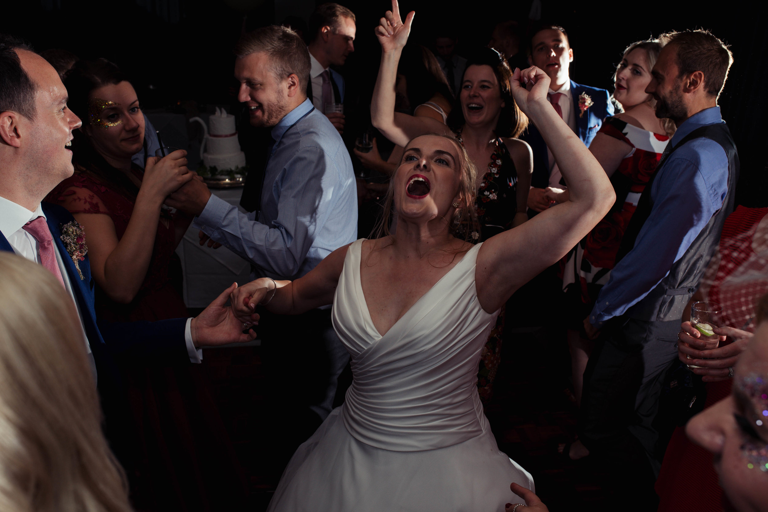 The bride letting her hair down with her friends on the dance floor