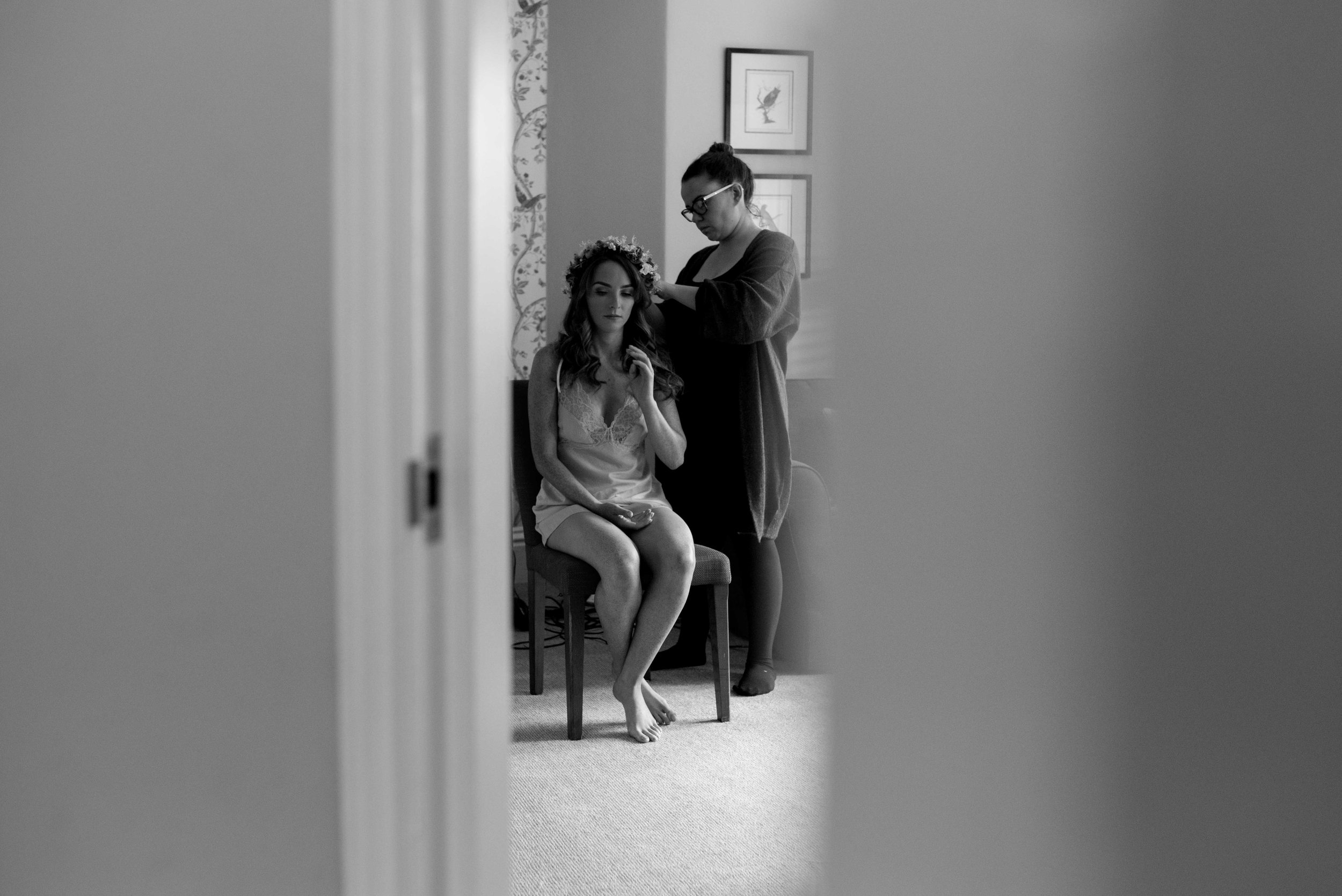 Bride sitting in the door way having her hair done