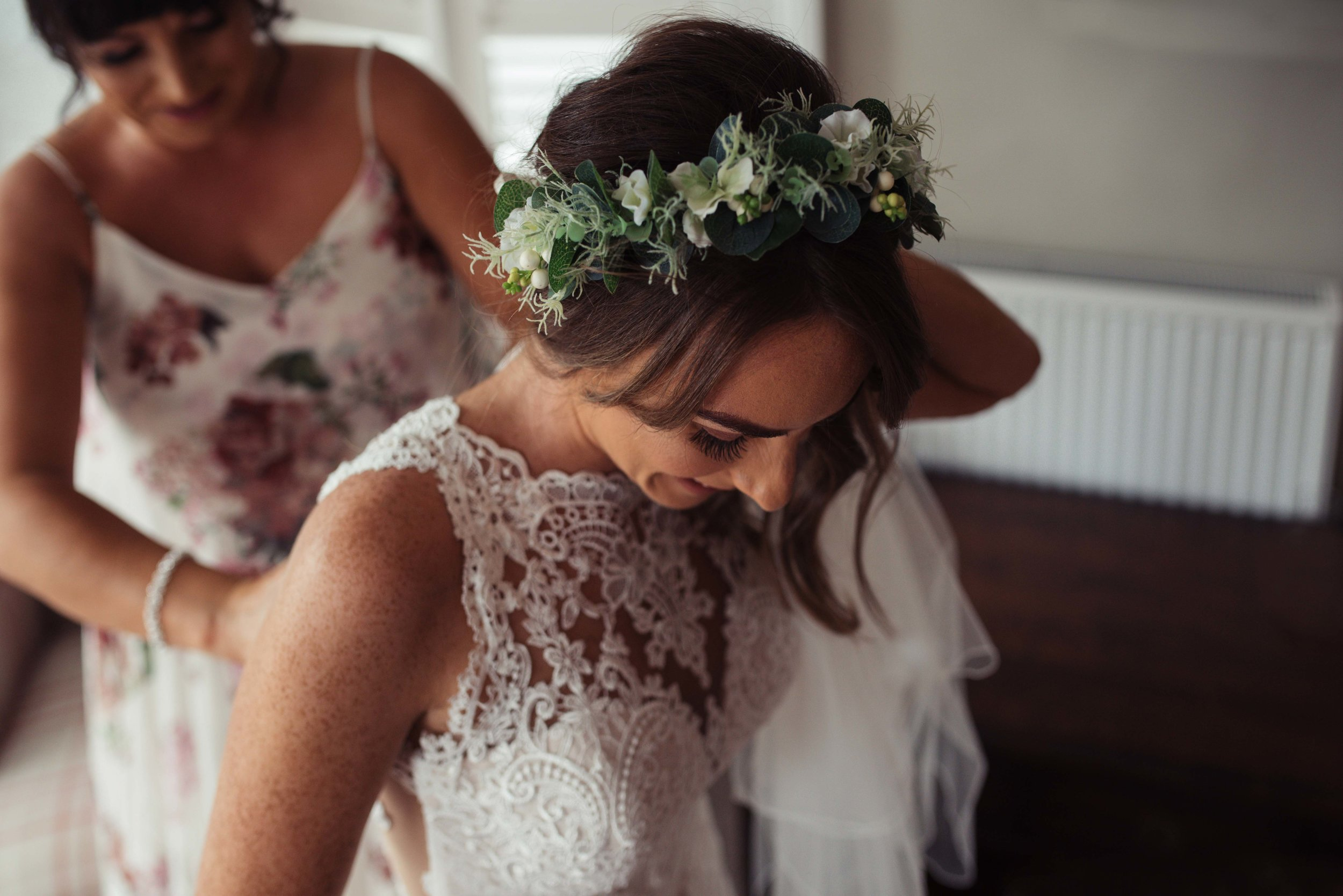 The bride smiles as her sister helps her into her lace wedding dress