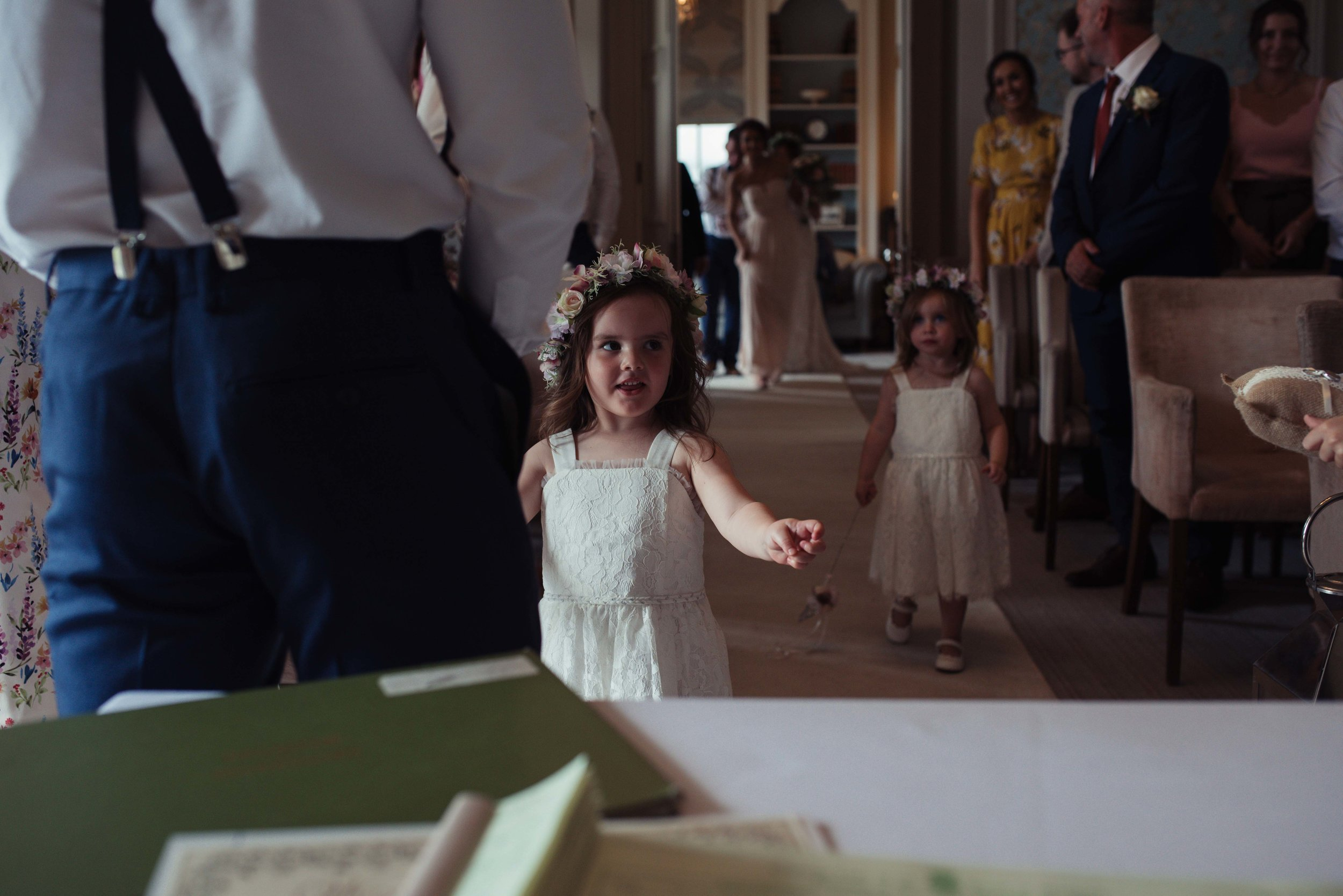 The flower girl, daughter of the bride and groom, walks up the aisle to her dad