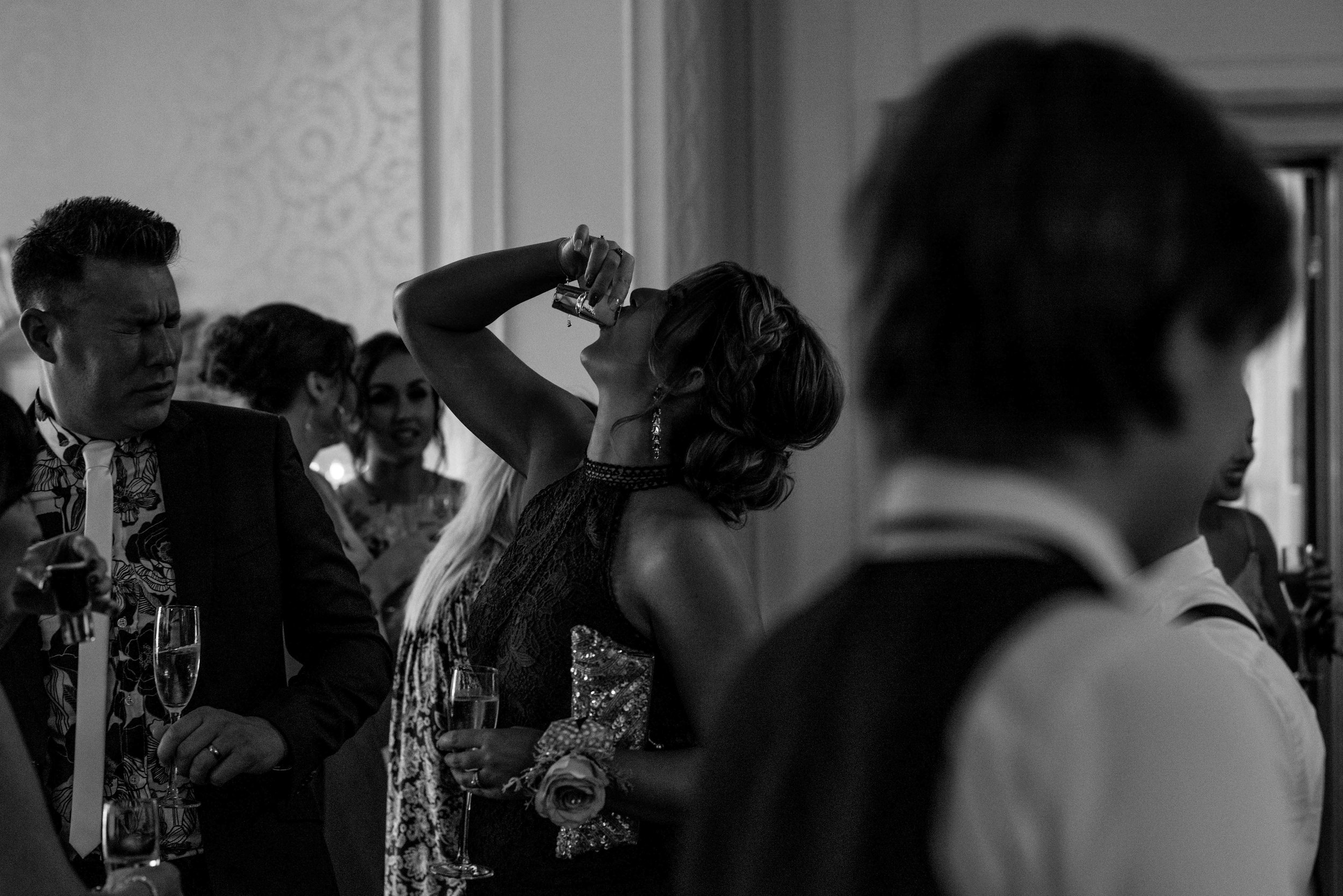 A wedding guest puts her head back to swallow a vodka shot