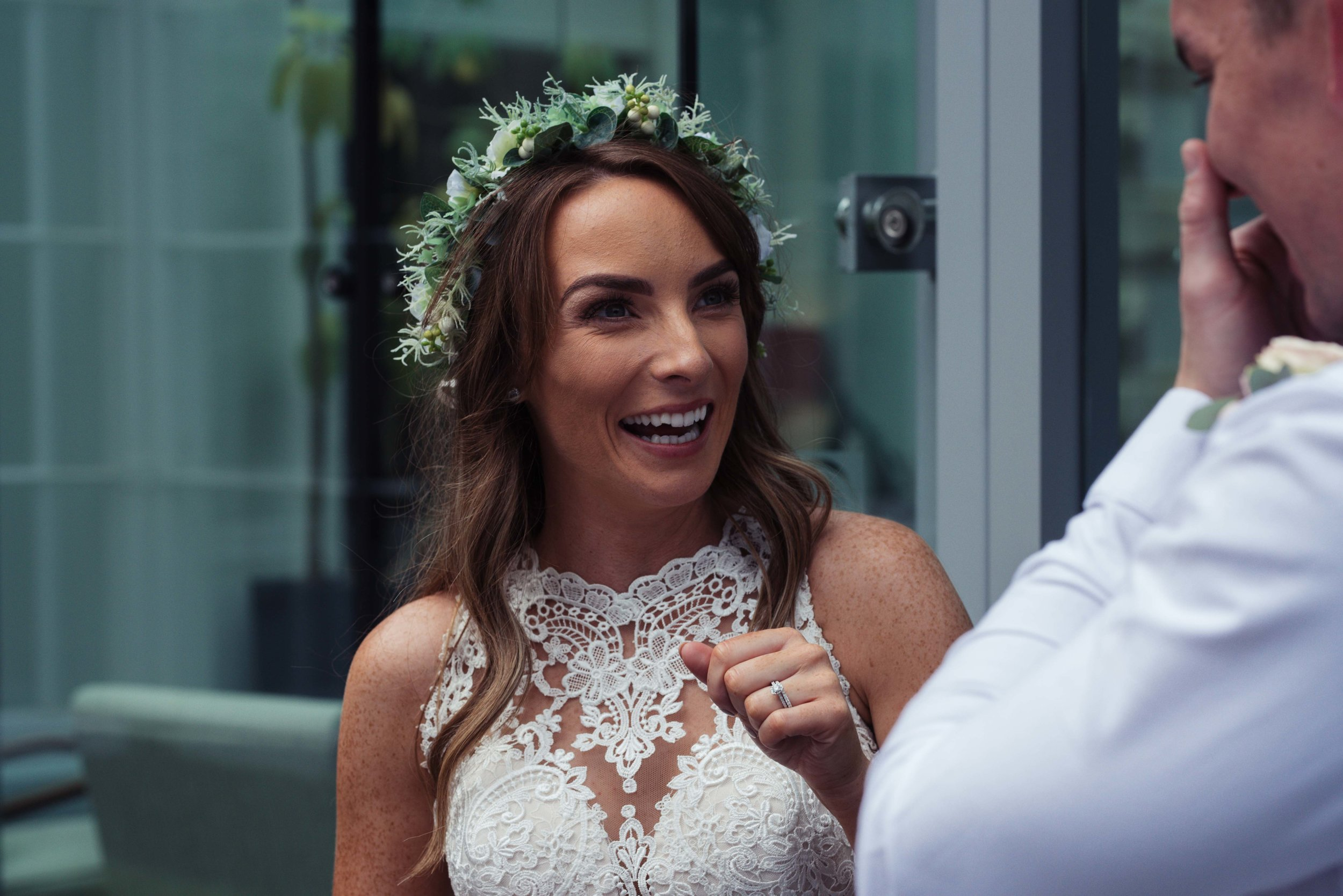 The bride stands outside the belsfield and has a giggle with her brother