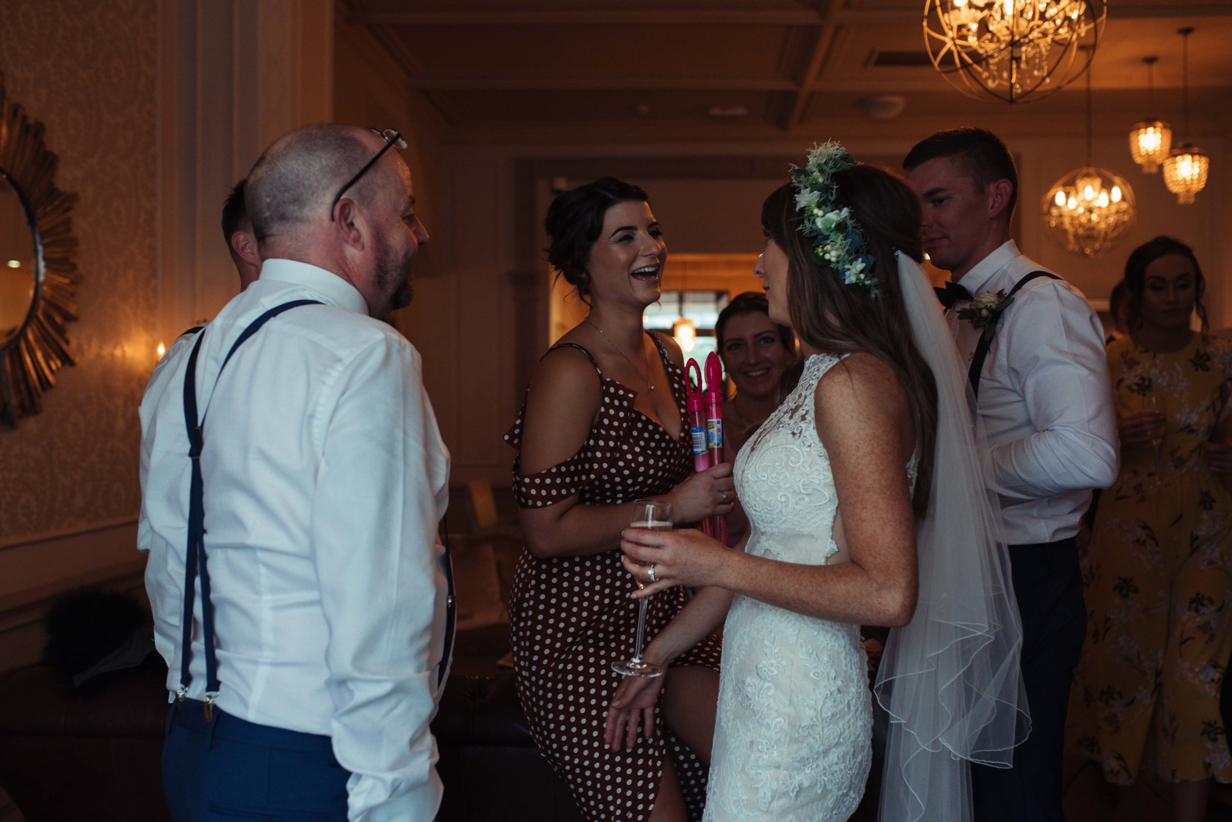 The bride stands and talks to friends in the bar at The Belsfield