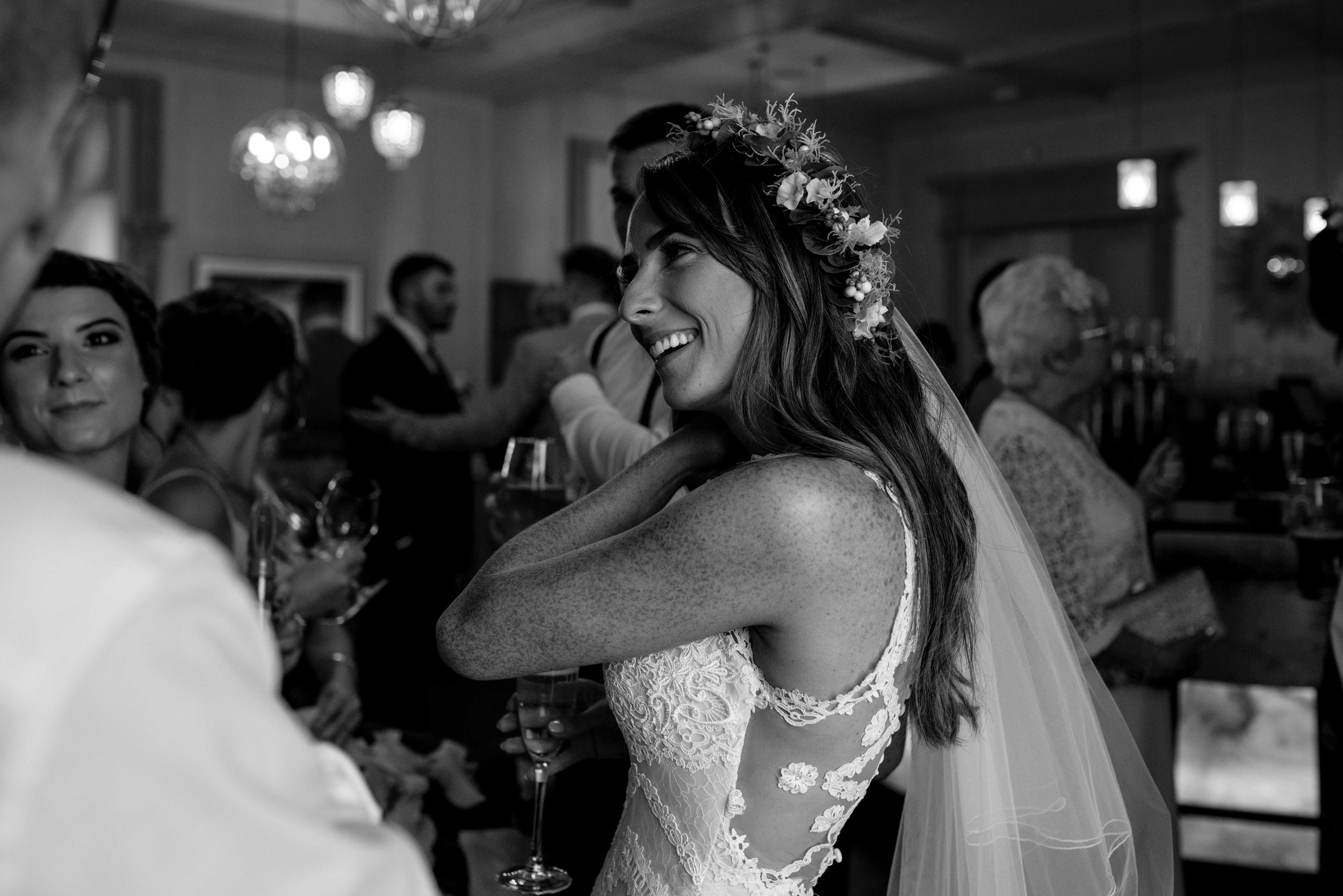 The bride wipes away a laughing tear as she chats to her friends