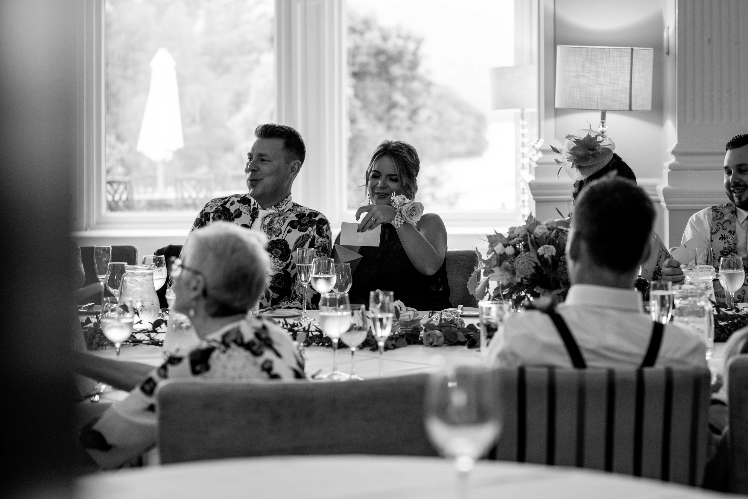 Two wedding guests with their backs facing the window laugh at a joke during the speeches