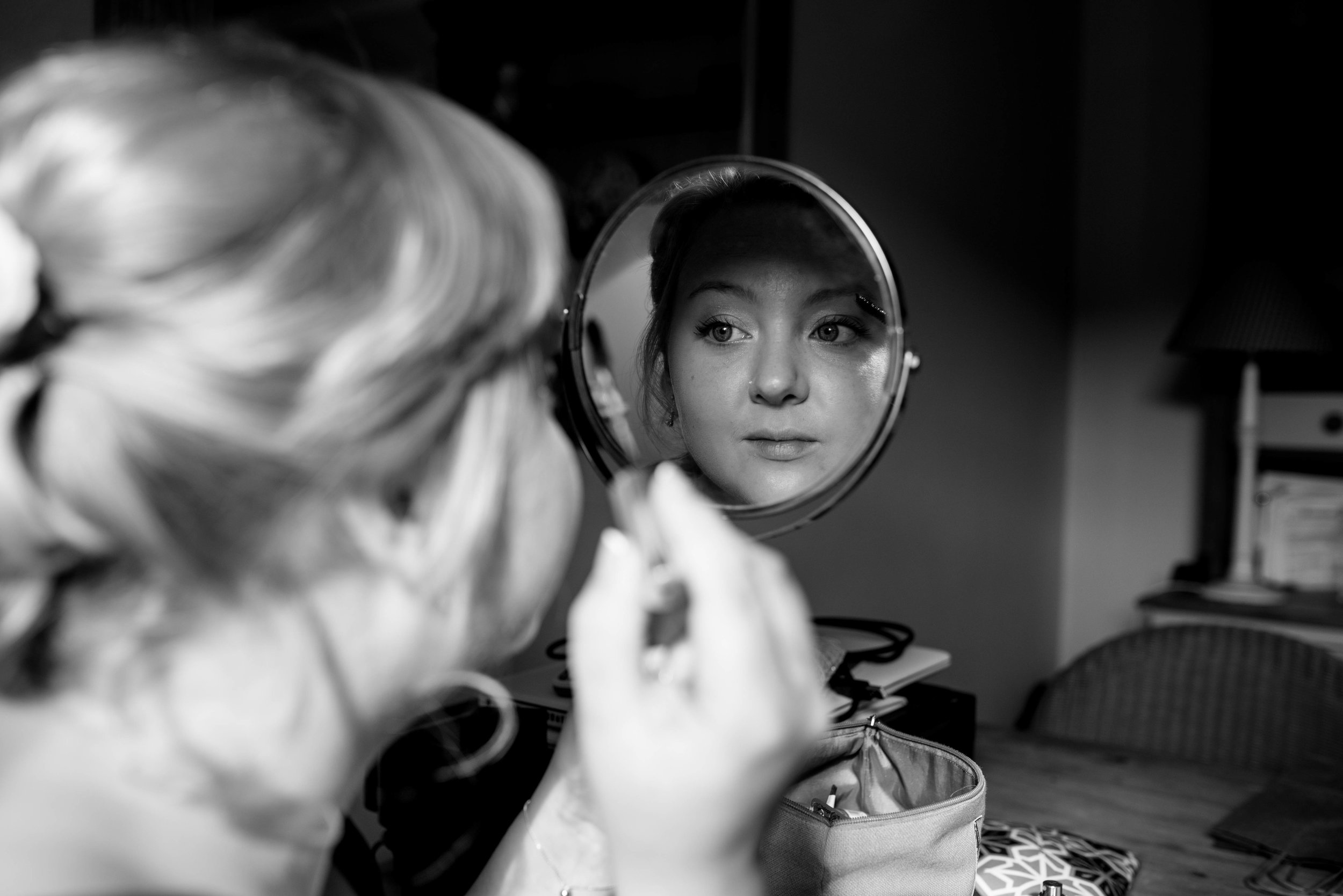 One of the bridemaids doing her makeup in a round mirror