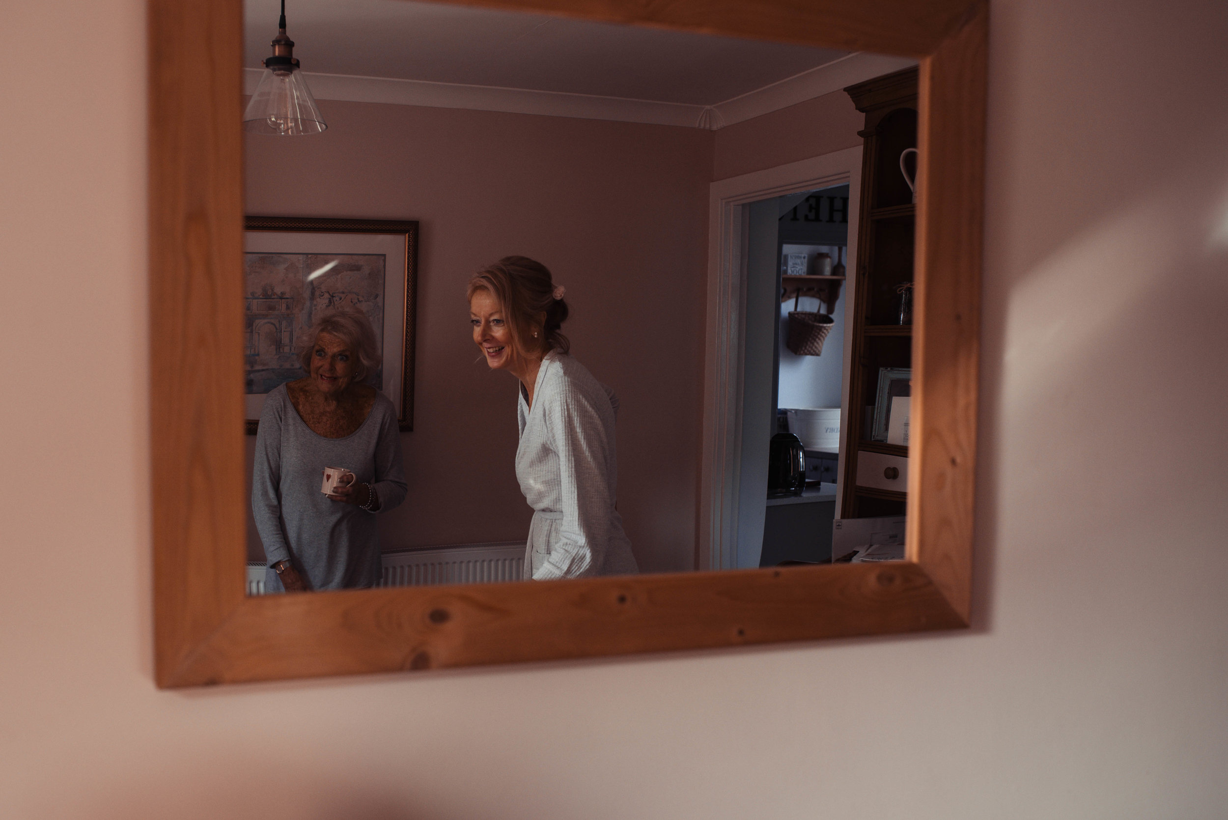 The bride and her mother as seen through a mirror in the kitchen dining room