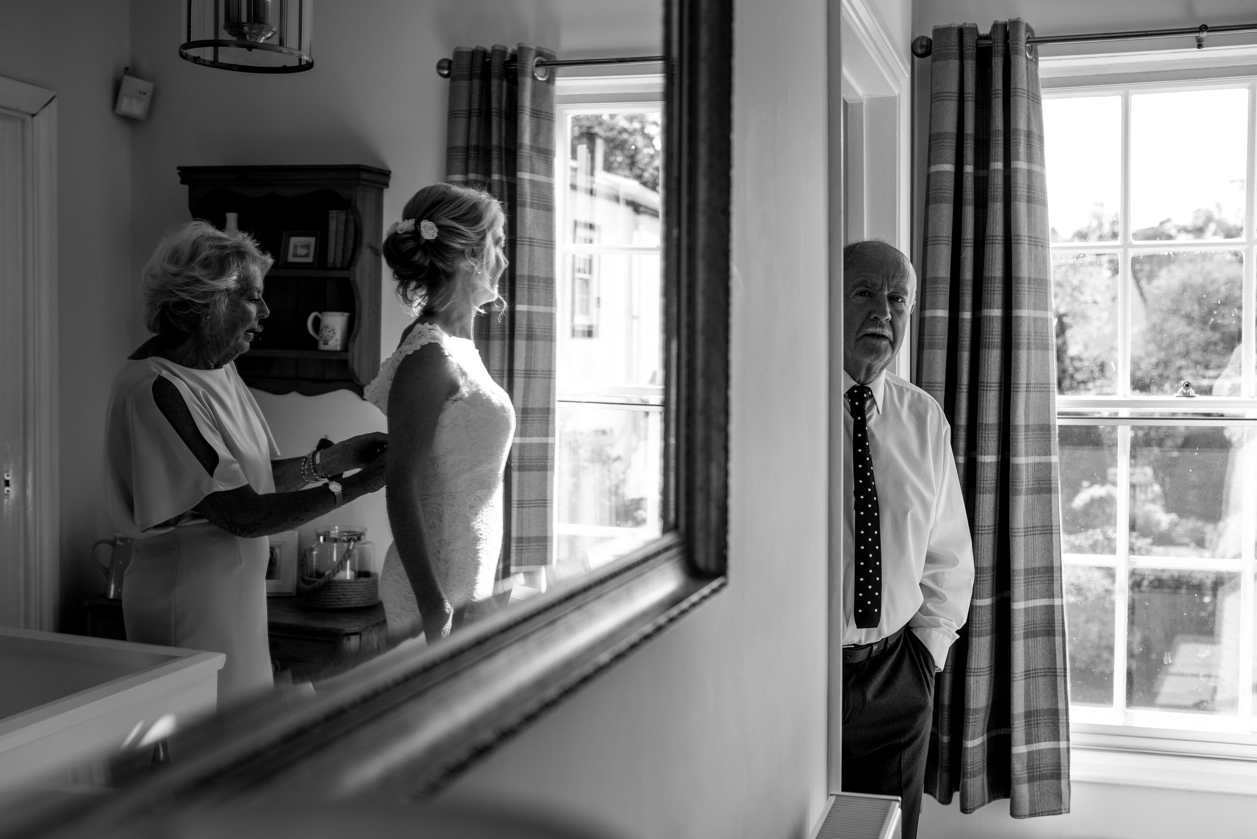 The brides father looks at the bride and her mother while she's getting dressed