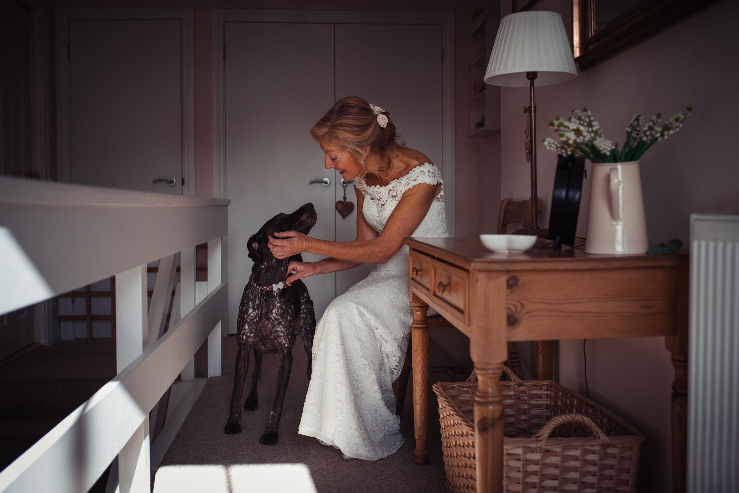 The bride sits on the top of the landing with her dog Lucy