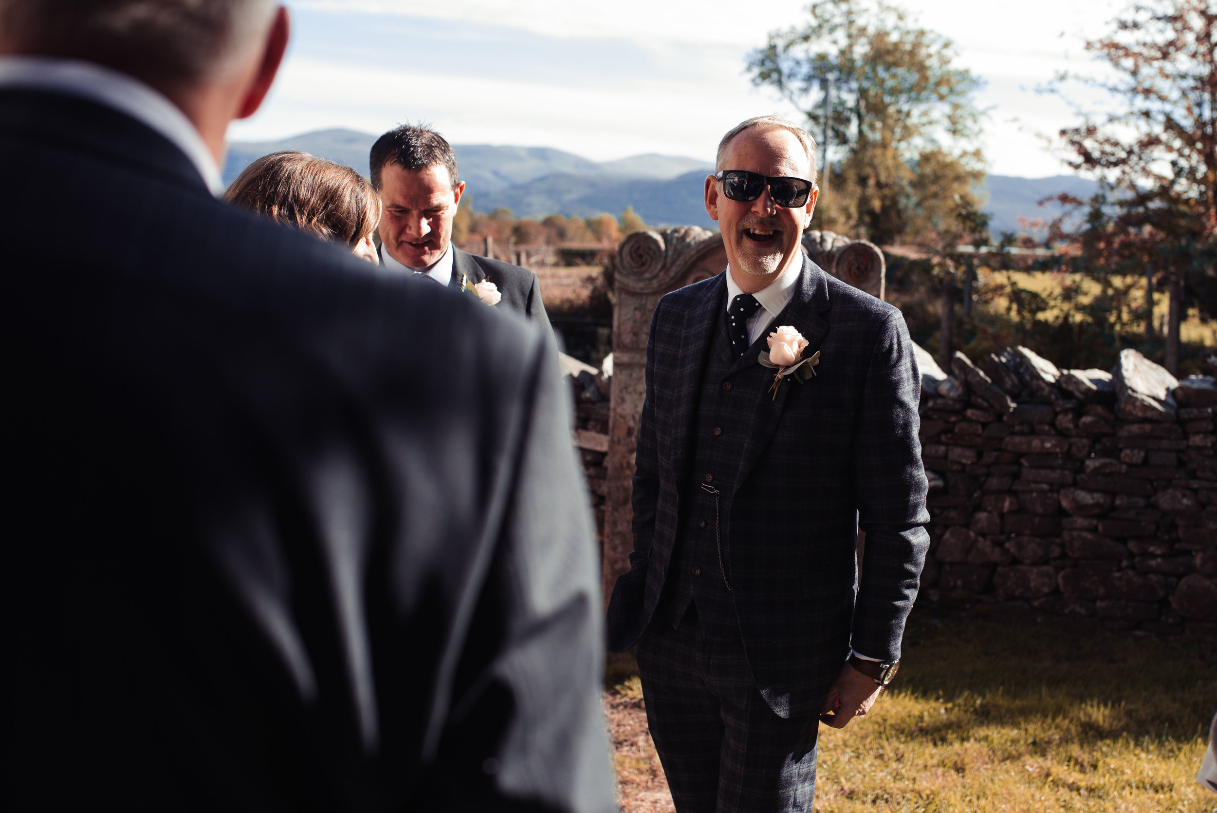 The groom chats with friends outside the lake District Church