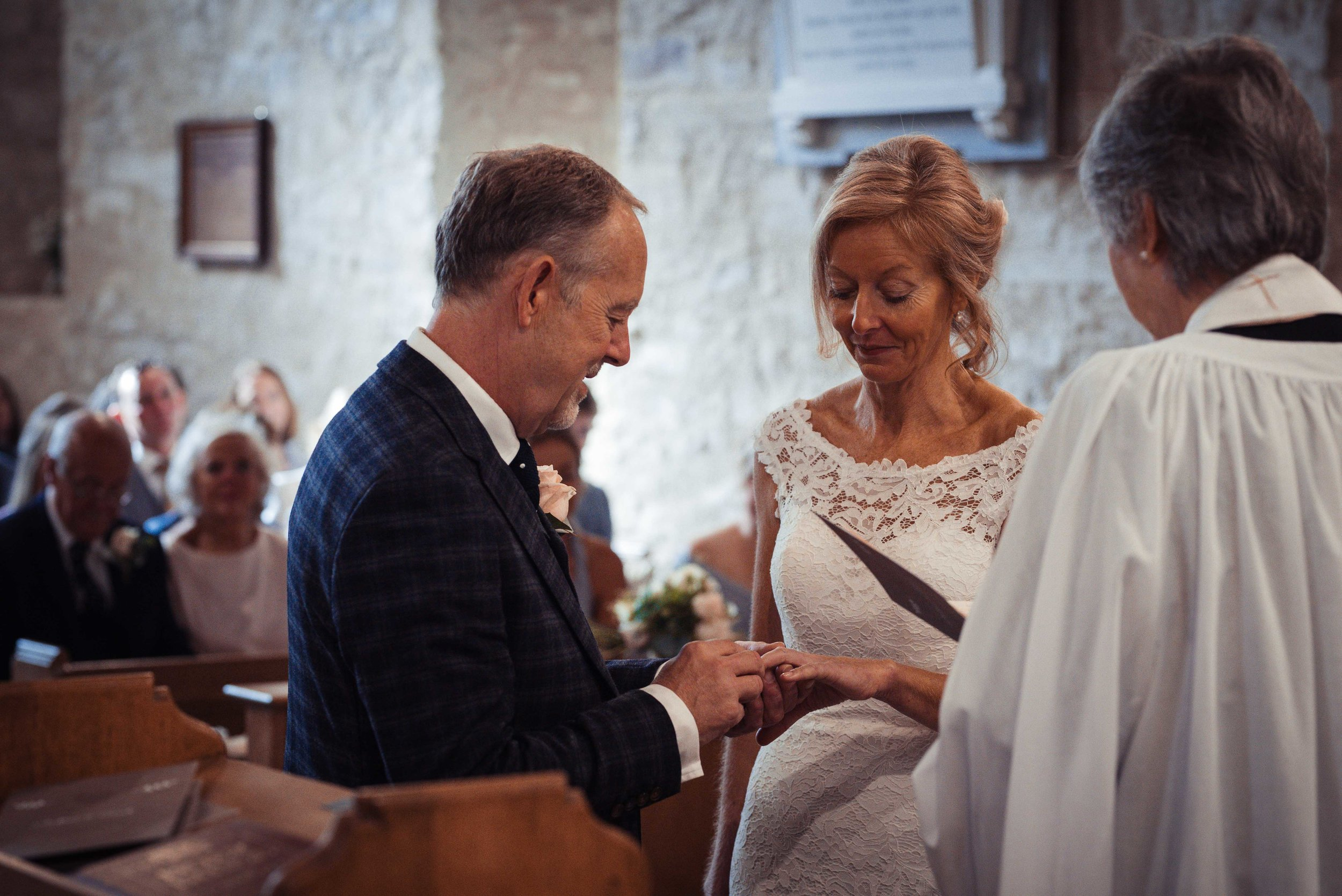 The bride and groom exchange rings during their lake district wedding