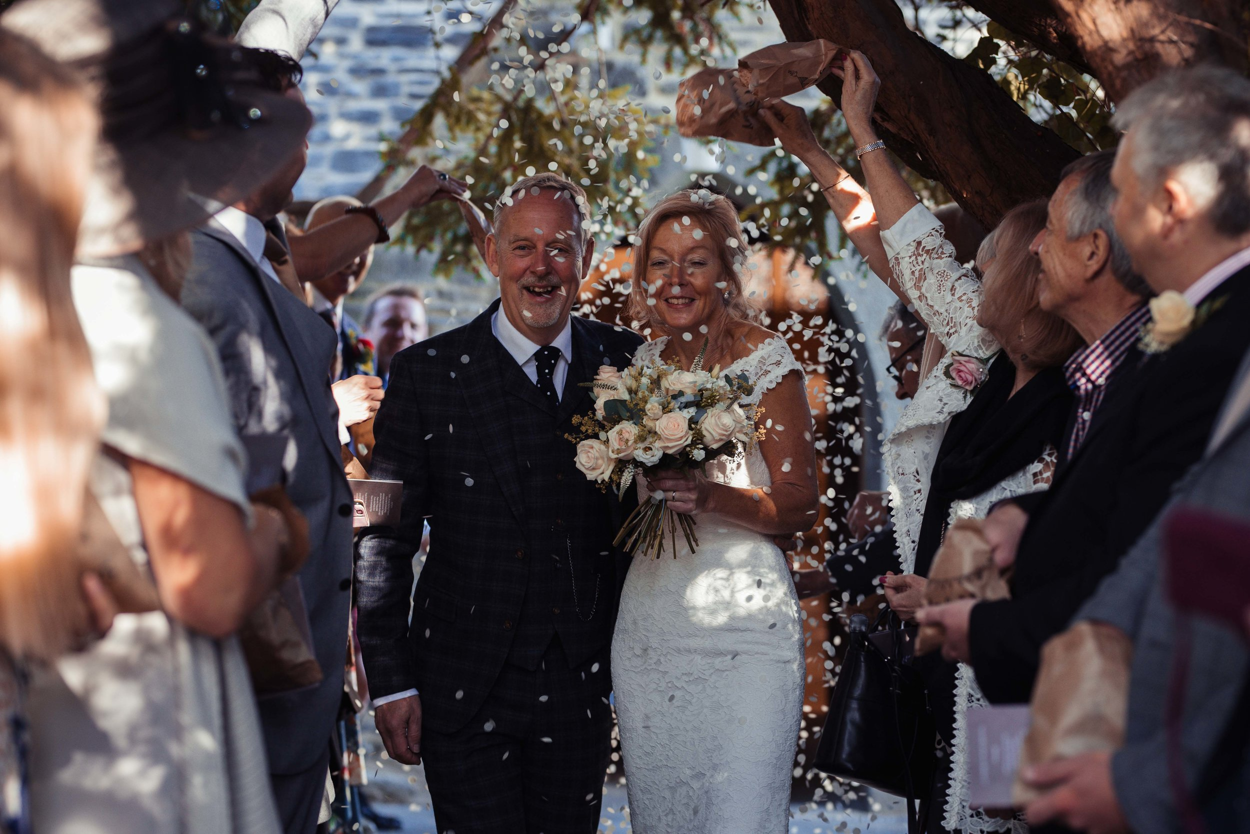 The bride and groom walk through a big sea of confetti outside their Cumbrian church