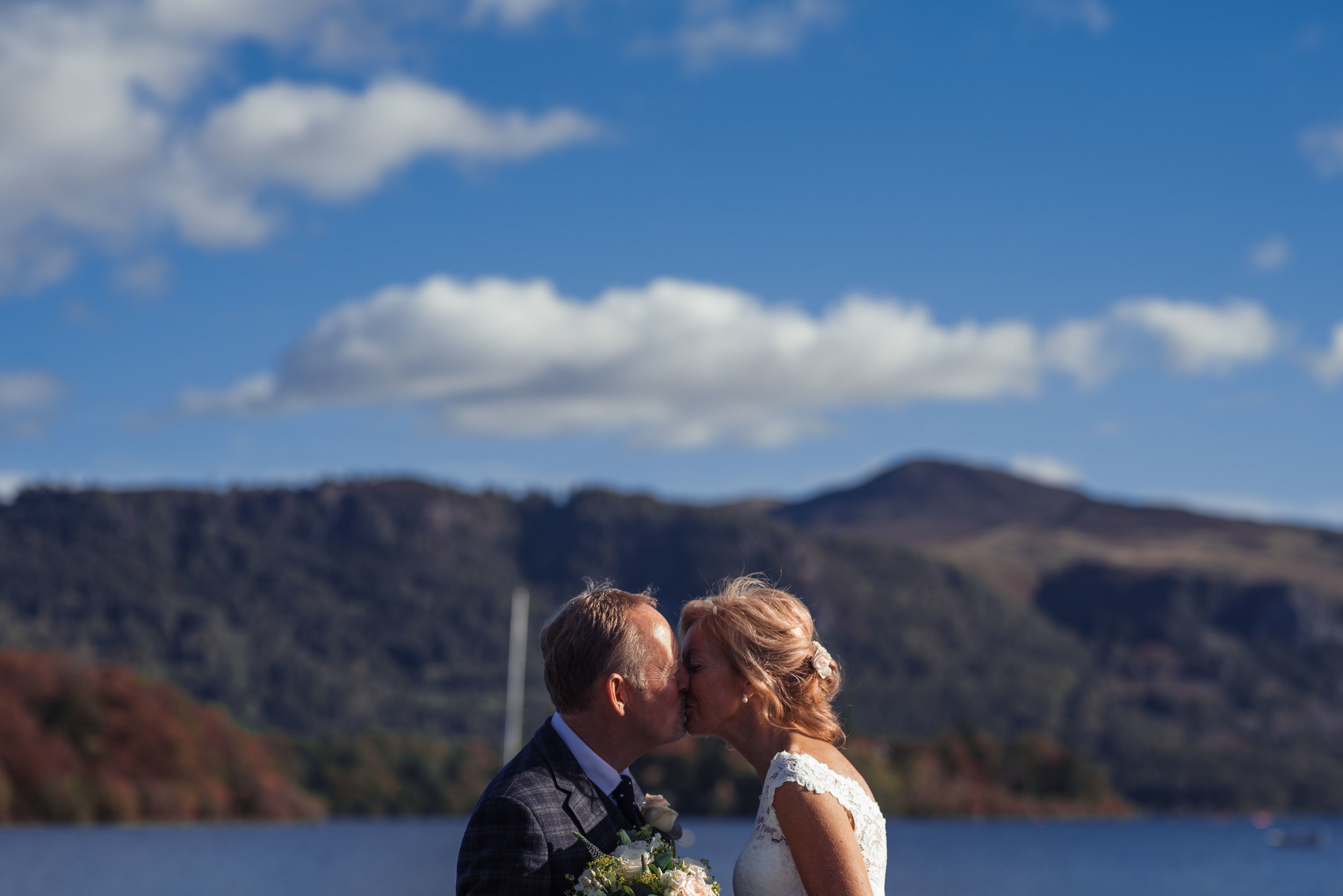The bride and groom share a kiss during their lake district wedding photography