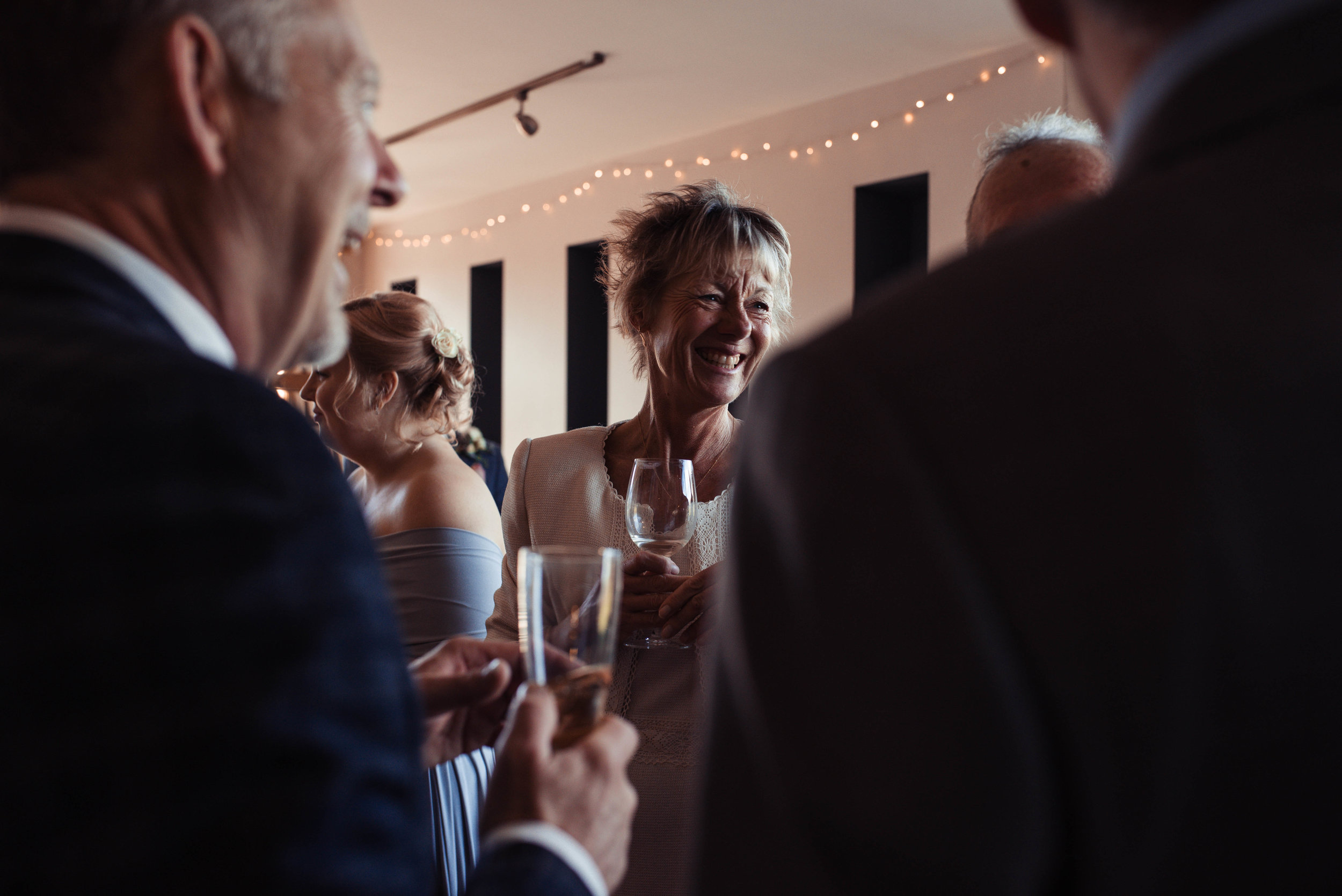 A female wedding guest dressed in a cream suit laughs at a joke one of the other guests tells