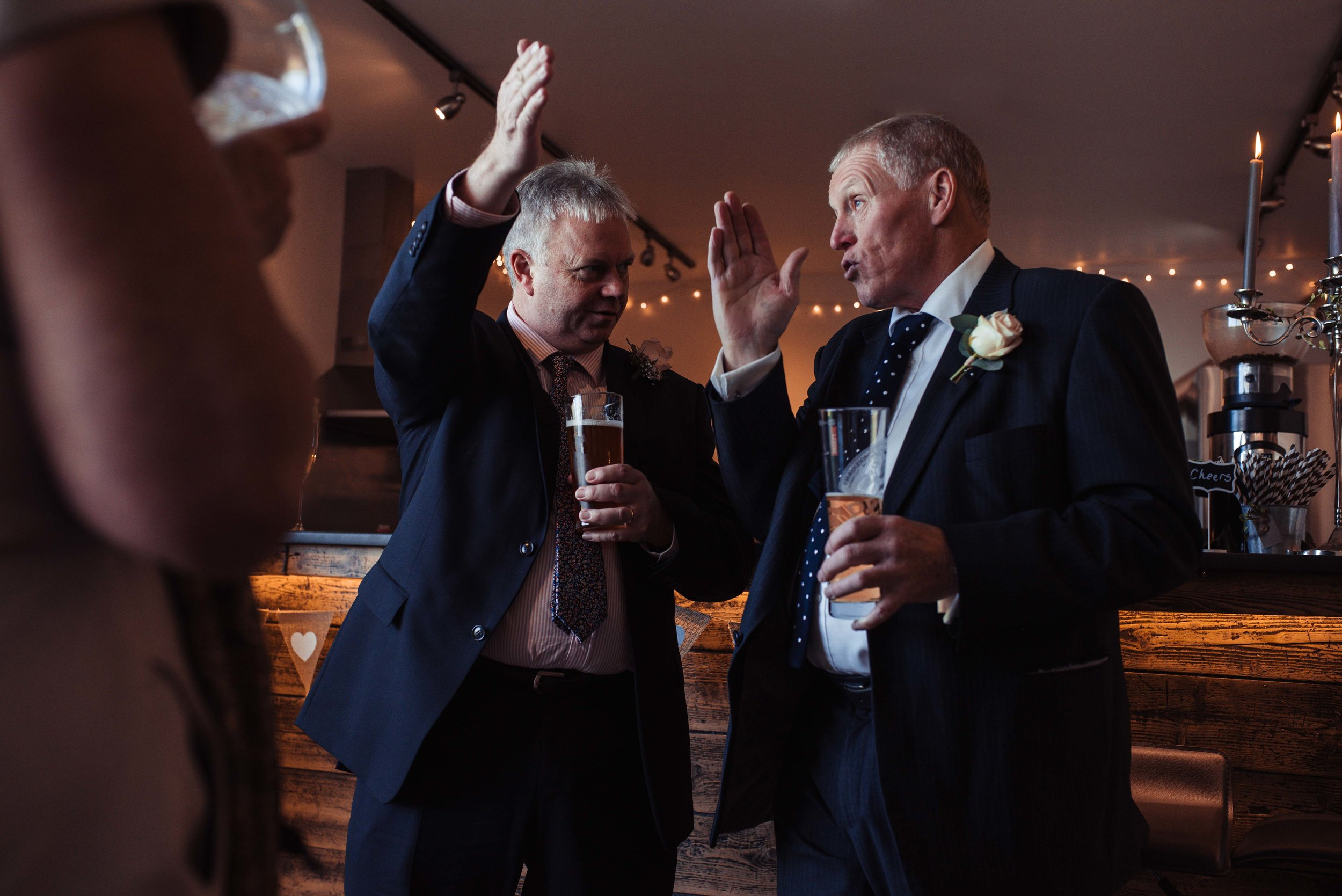 Two wedding guests standing at the bar use hand signals