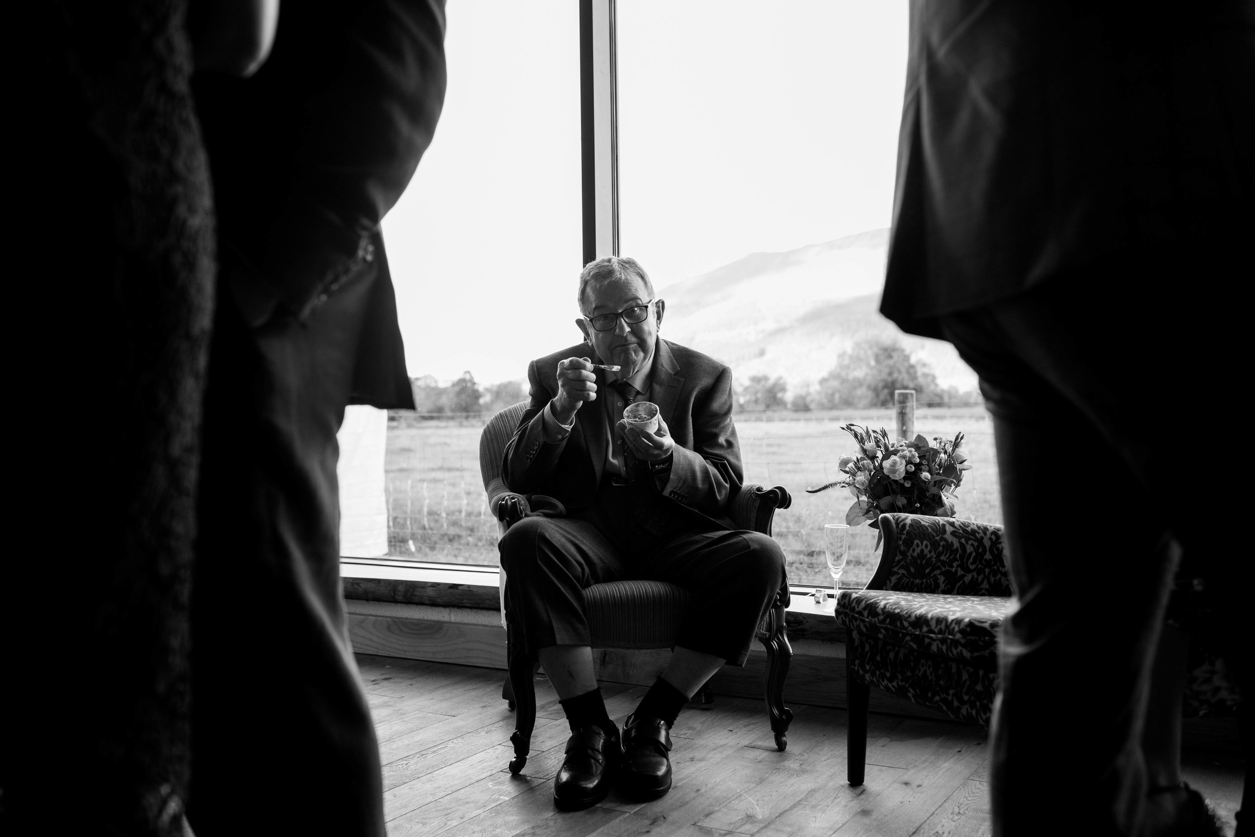 A male wedding guest sits by the window to eat his ice cream