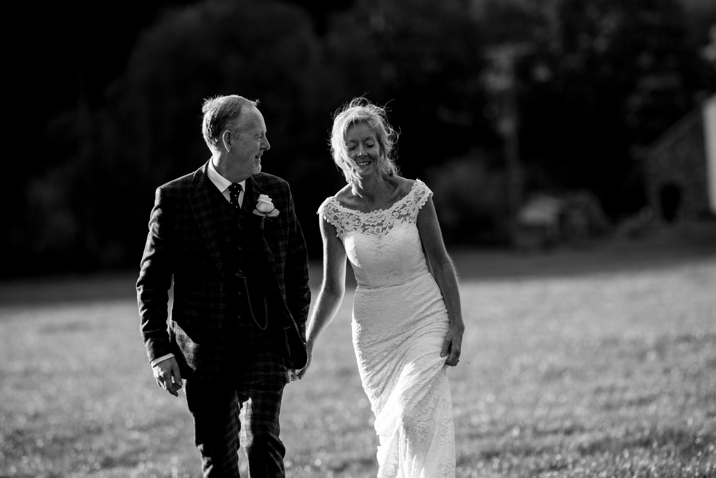 A black and white image of the bride and groom walking towards the camera