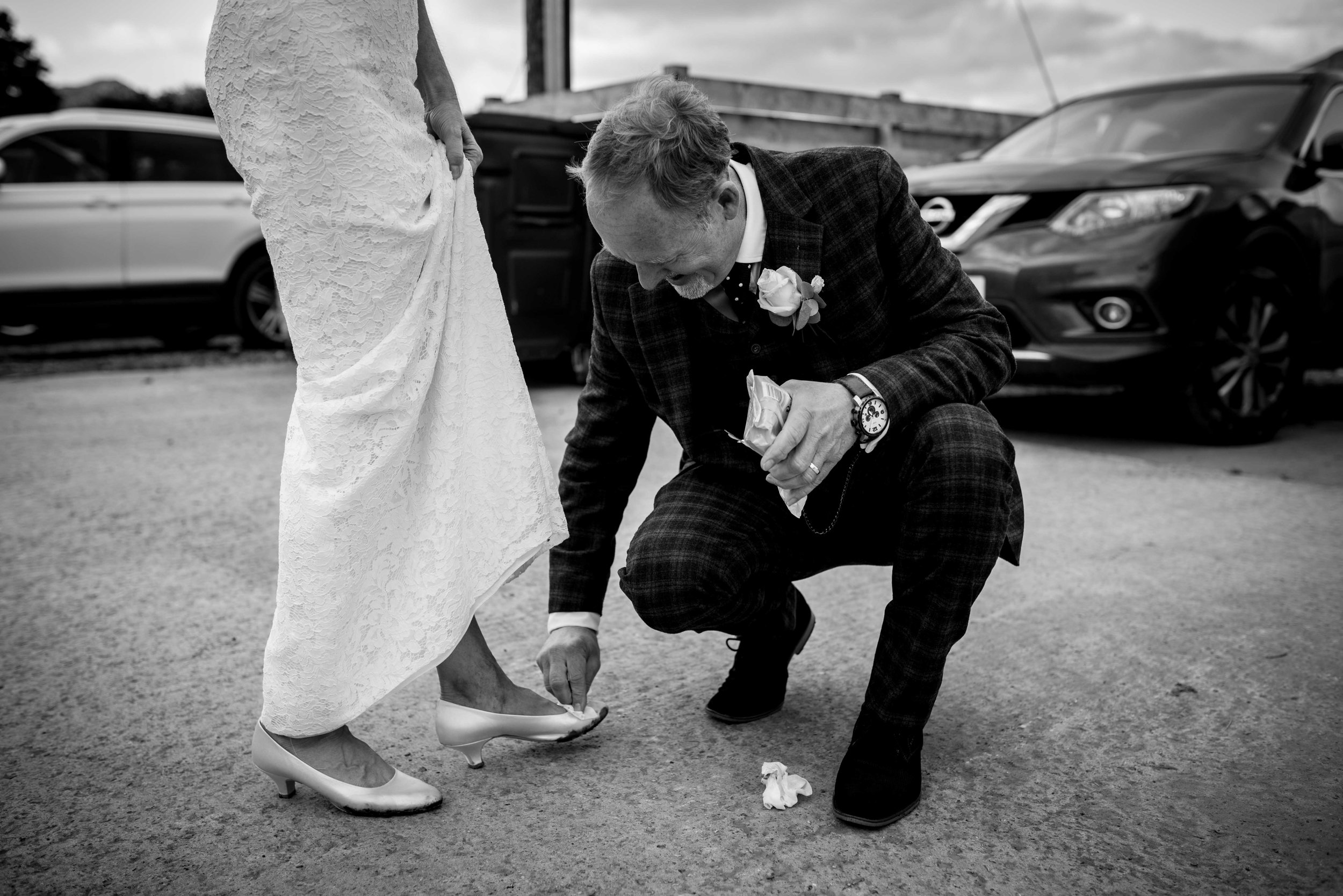 The groom stoops to clean mud off the brides shoes