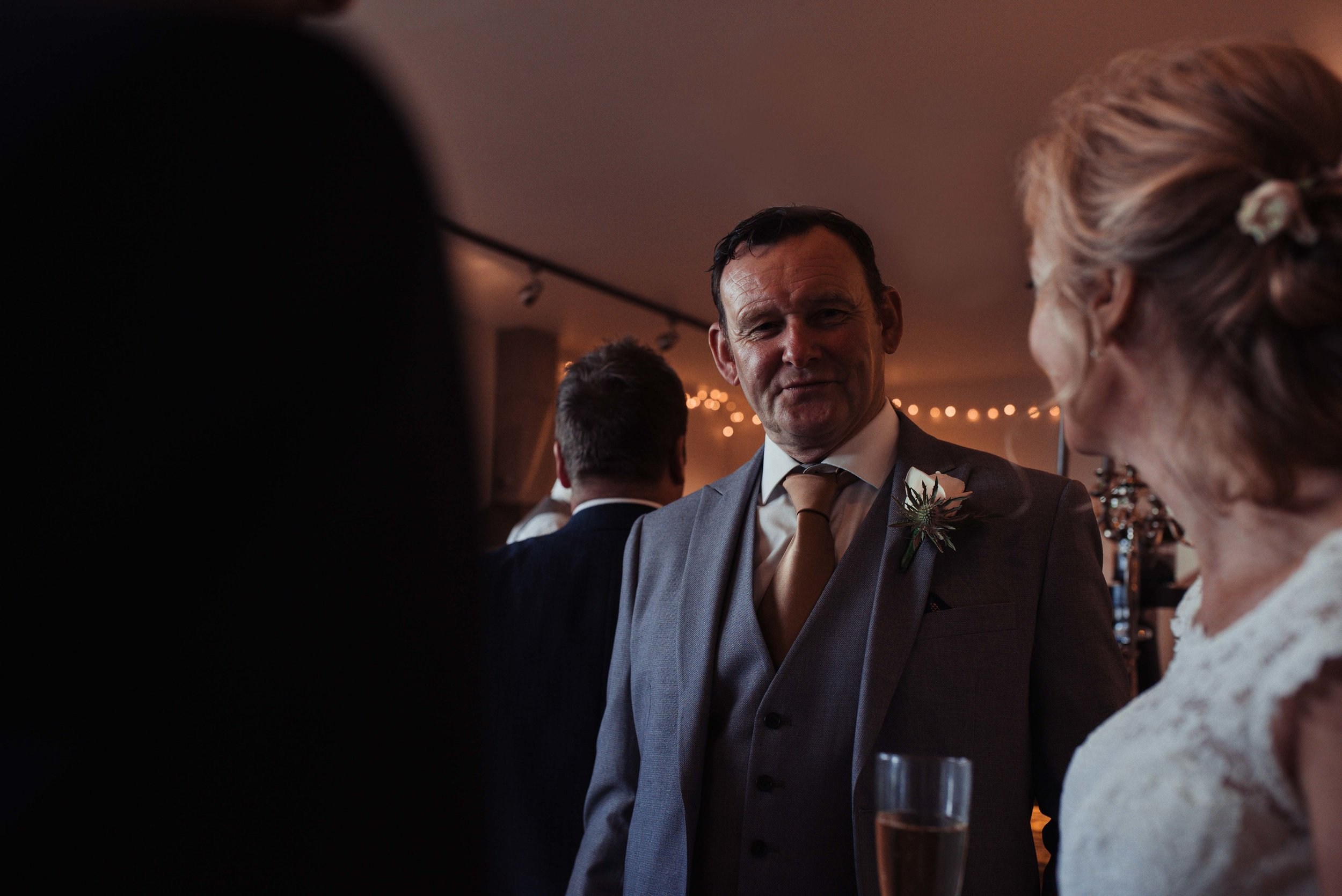 A male wedding guest standing talking to other guests inside the wedding venue